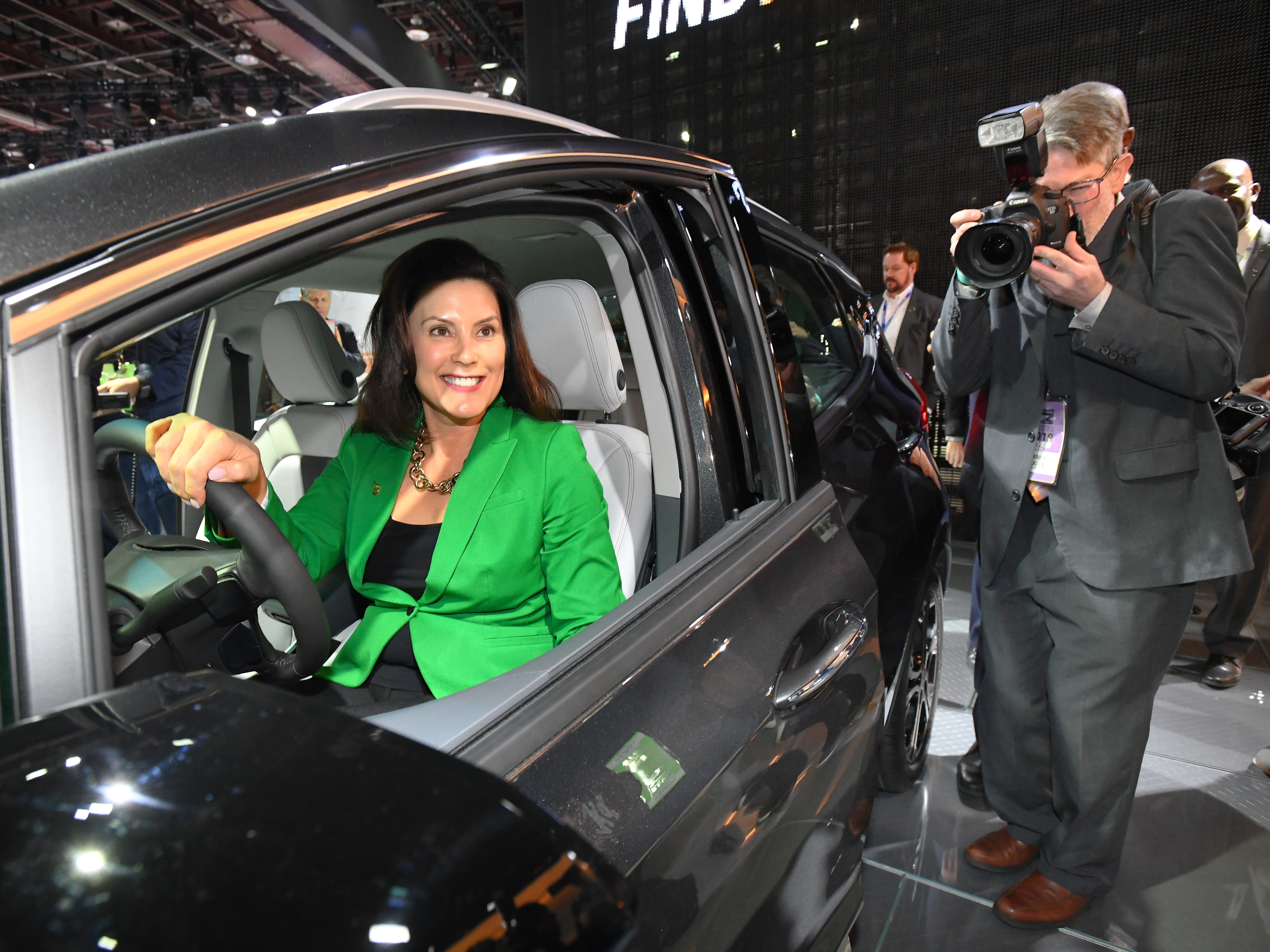 Members of the media follow around Michigan Governor Gretchen Whitmer, here trying out a Chevrolet Bolt EV, during a tour of the North American International Auto Show.