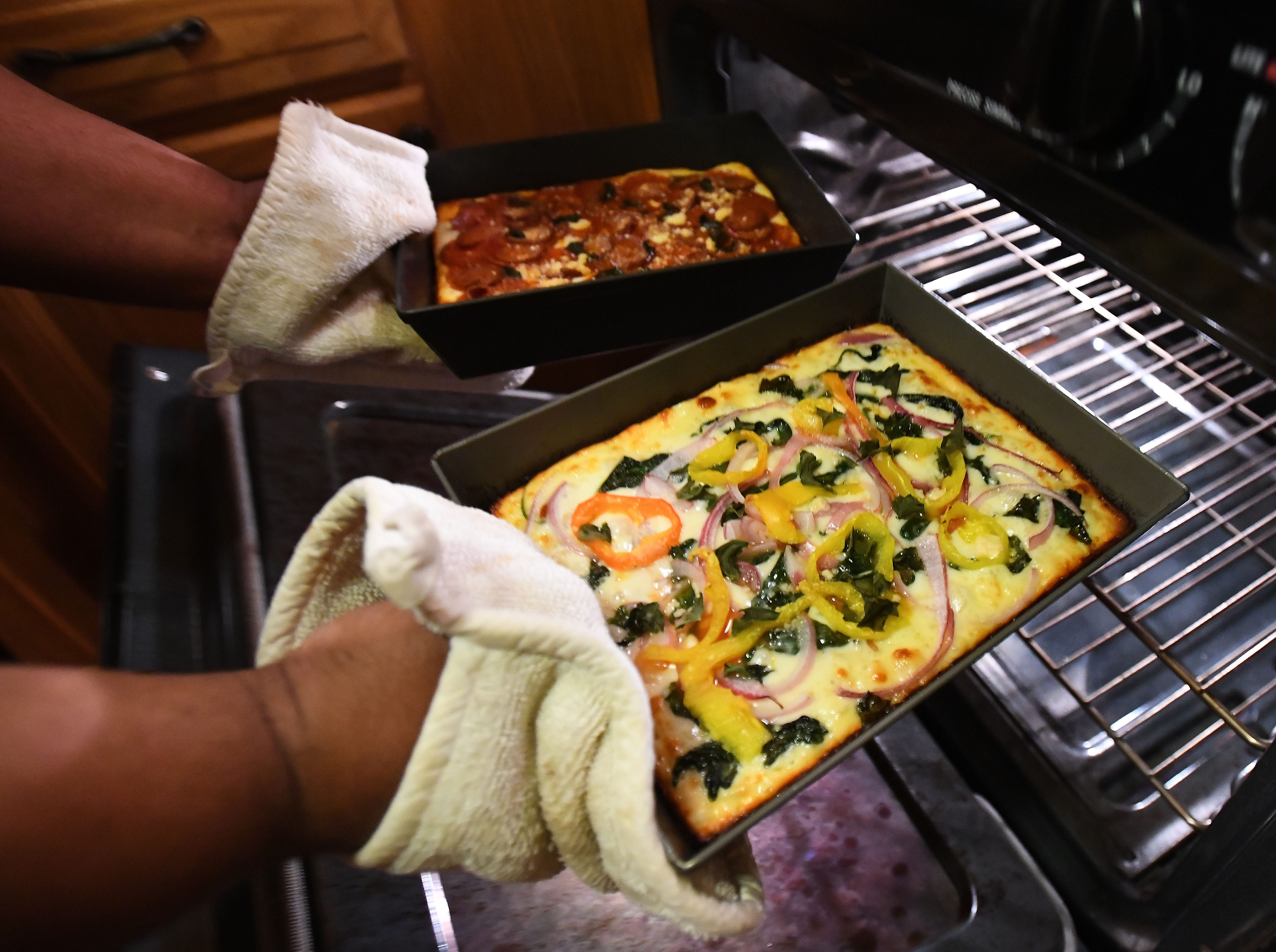 Instachef Cliff Skighwalker takes out a pepperoni and sausage pizza and a veggie pizza at his home in Pontiac.
