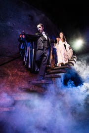 """The Phantom (Quentin Oliver Lee) leads Christine (Eva Tavares) down into his subterranean lair in """"Phantom of the Opera"""" at the Detroit Opera House."""