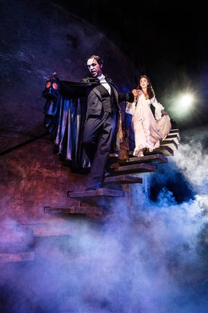 "The Phantom (Quentin Oliver Lee) leads Christine (Eva Tavares) down into his subterranean lair in ""Phantom of the Opera"" at the Detroit Opera House."