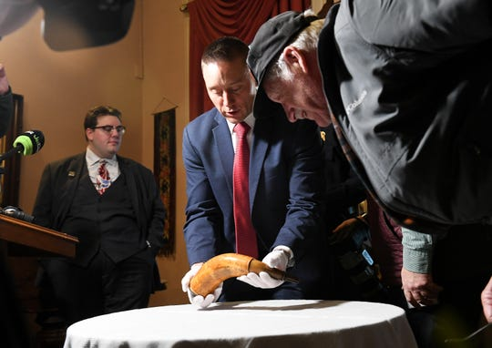 FBI special agent Jake Archer of the FBI Art Crime team holds the powder horn after the press conference while John Bendzick of Dearborn, right, looks on. The 1757 powder horn was stolen from the  Dearborn Historical Museum in Dearborn, Mich. in 1952 and returned to it on Jan. 15, 2019.  It  was tracked down by Dearborn police and the FBI Art Crime Team.