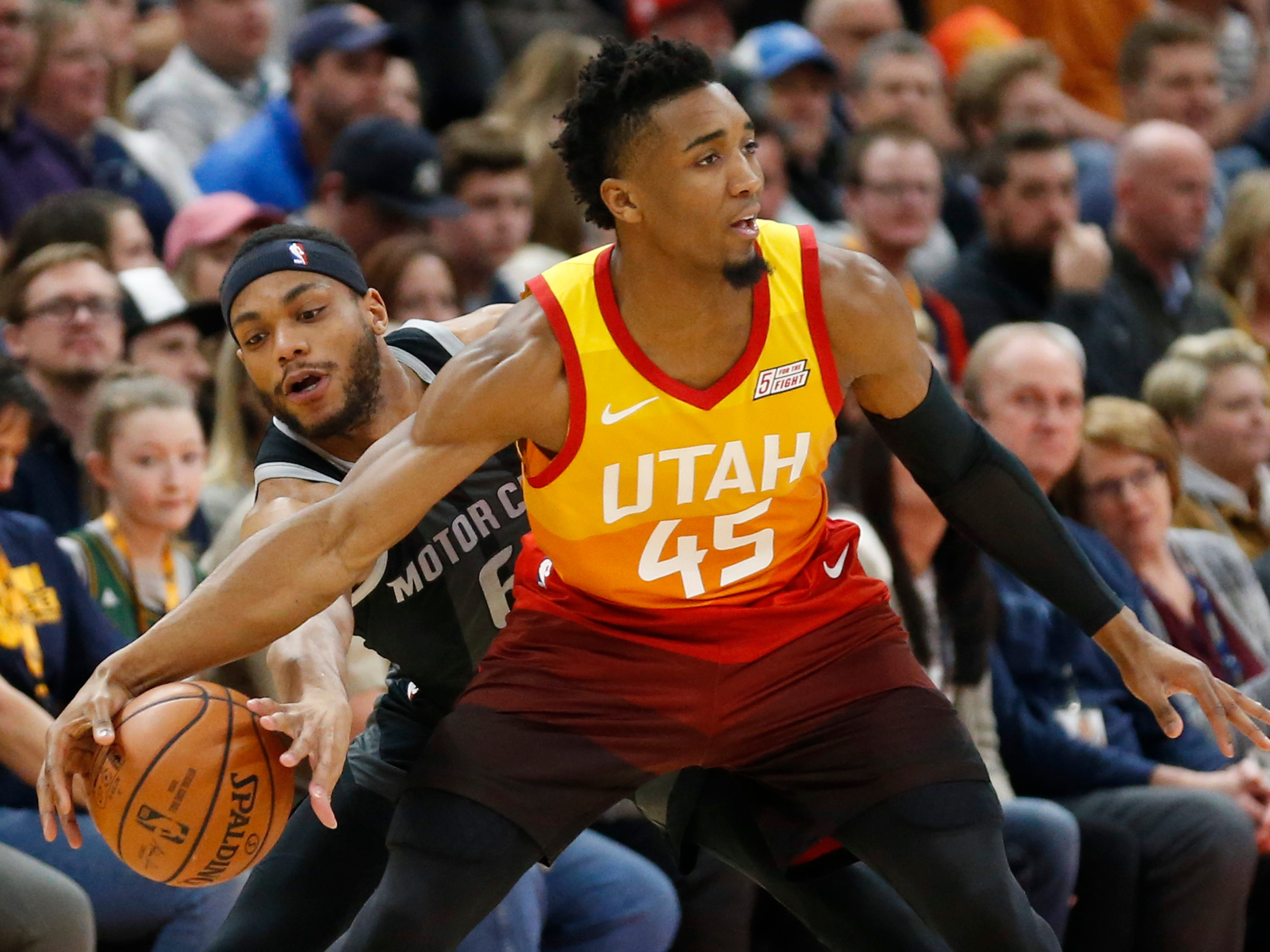 Detroit Pistons guard Bruce Brown, left, attempts a steal from Utah Jazz guard Donovan Mitchell (45) during the first half.