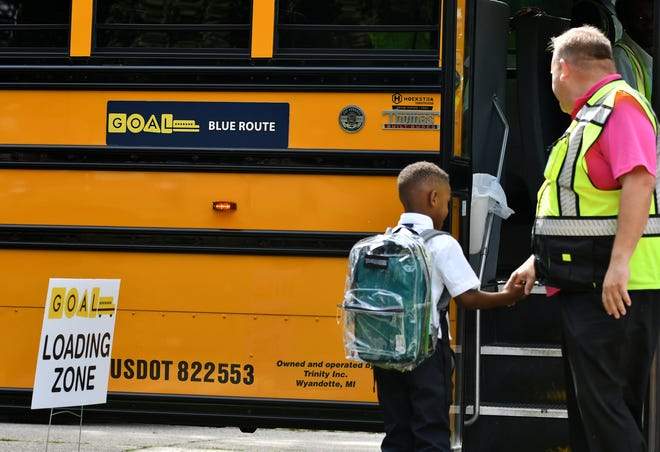 Trinity Transportation general manager Joel Matanzas shakes hands with a student before he gets on a Detroit GOAL line school bus at University Yes Academy in Detroit earlier this school year.