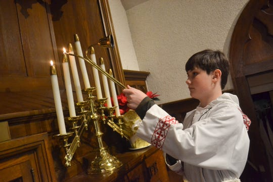 Tyler Rodrigue-Hejhal lights candles as part of his acolyte duties at St. Thomas' Episcopal Church in Port Clinton.