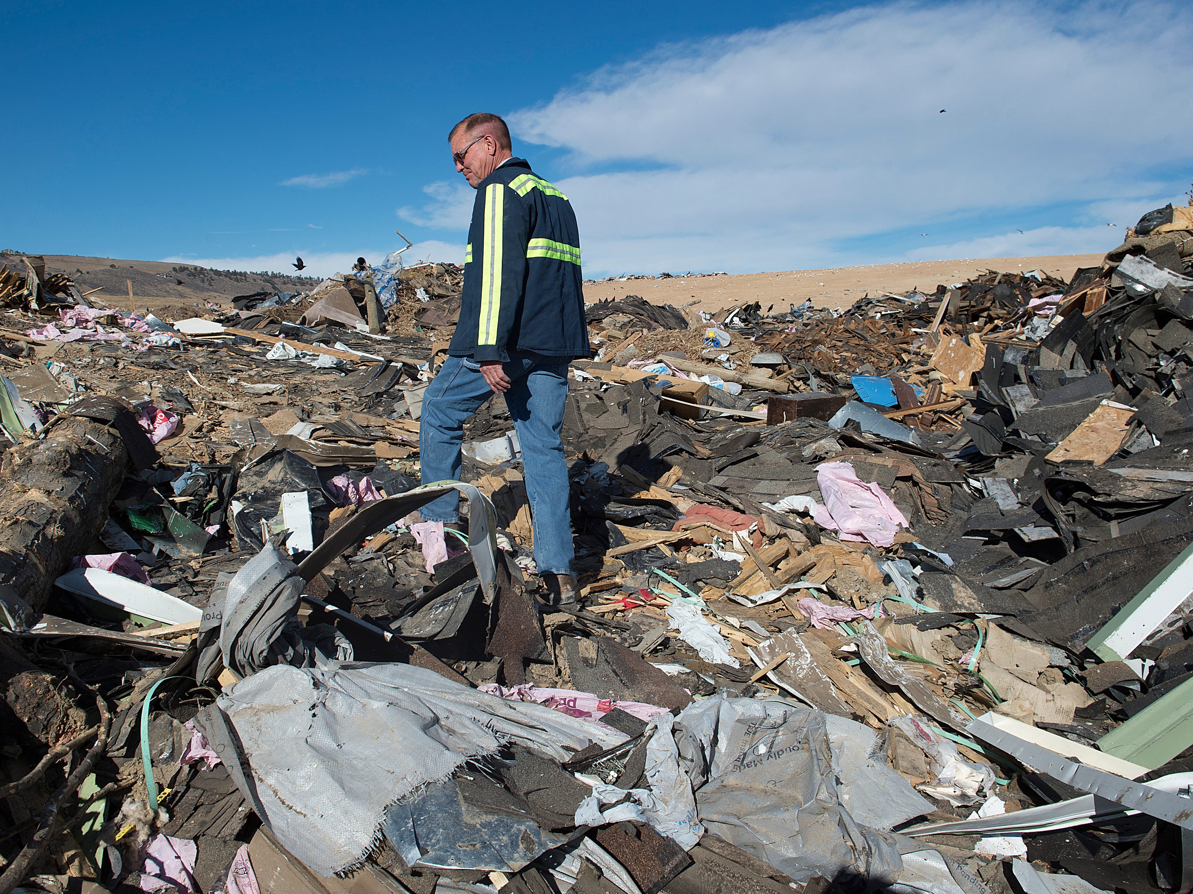 Assistant Director Jeff Boltz walks through piles of roofing materials and demolition waste at the Larimer County Landfill on Tuesday, January 15, 2019.