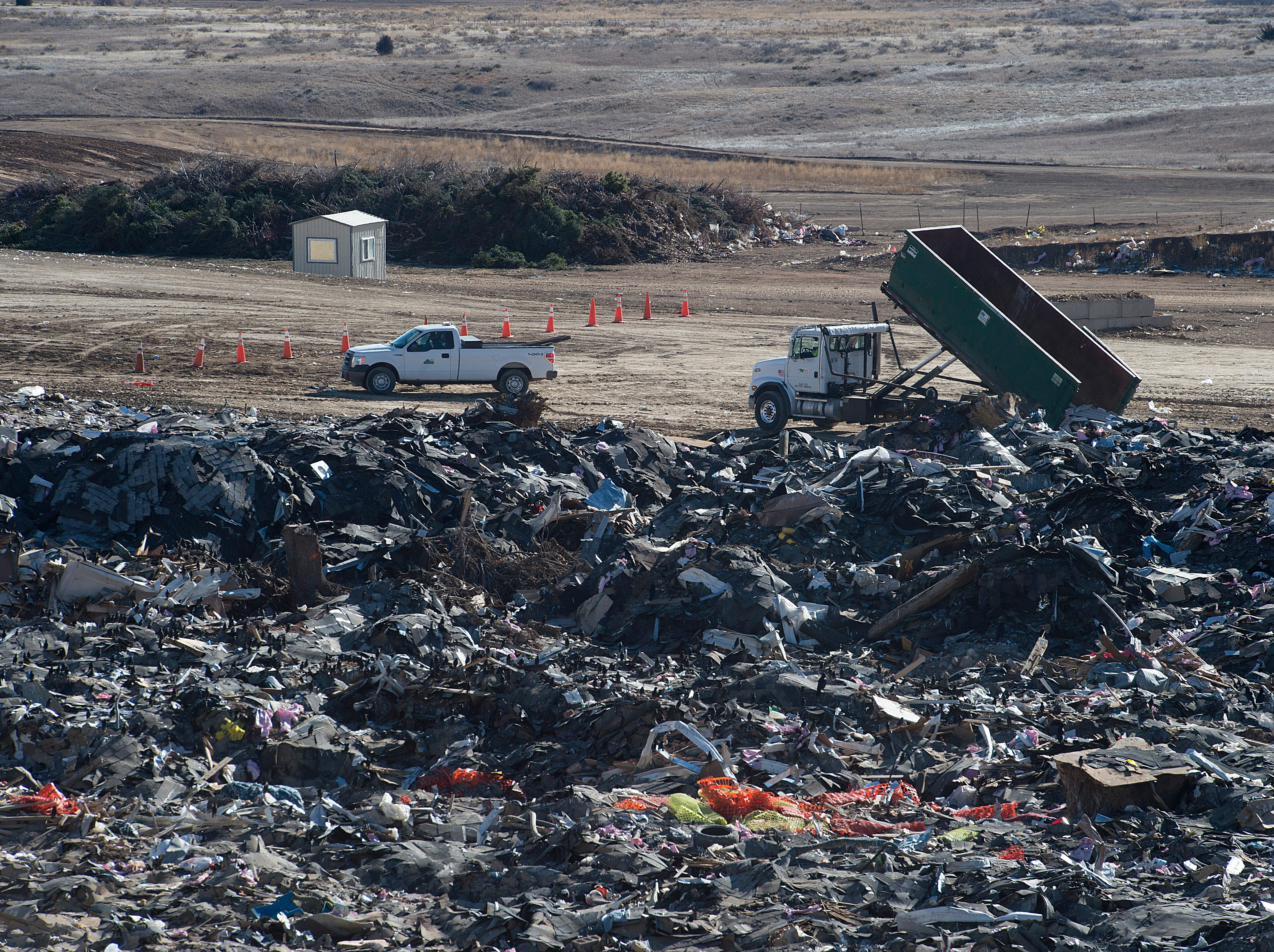 Trucks are dwarfed by piles of construction and demolition waste at the Larimer County Landfill on Tuesday, January 15, 2019.