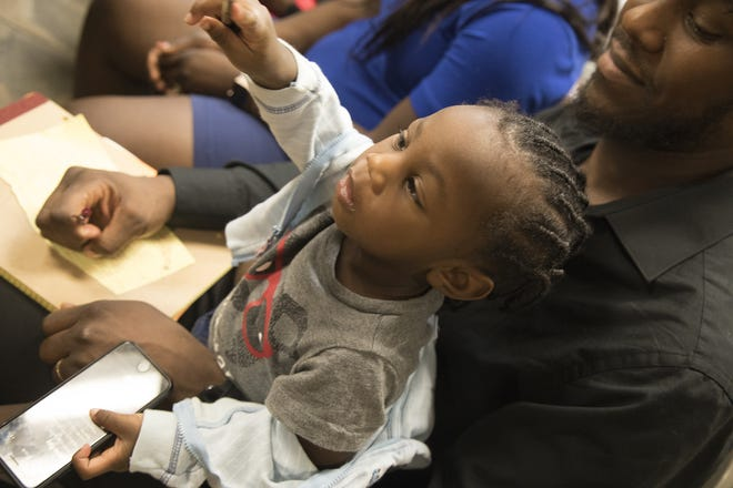 Brandon Addison of Fort Myers holds his one-year-old son at a Monday meeting where he and 37 other families learned they will be receiving relocation vouchers to find new affordable housing. Watersong Realty, which owns Sunrise Towers where Addision lives, decided to cancel the HUD contract that subsidizes their apartments.