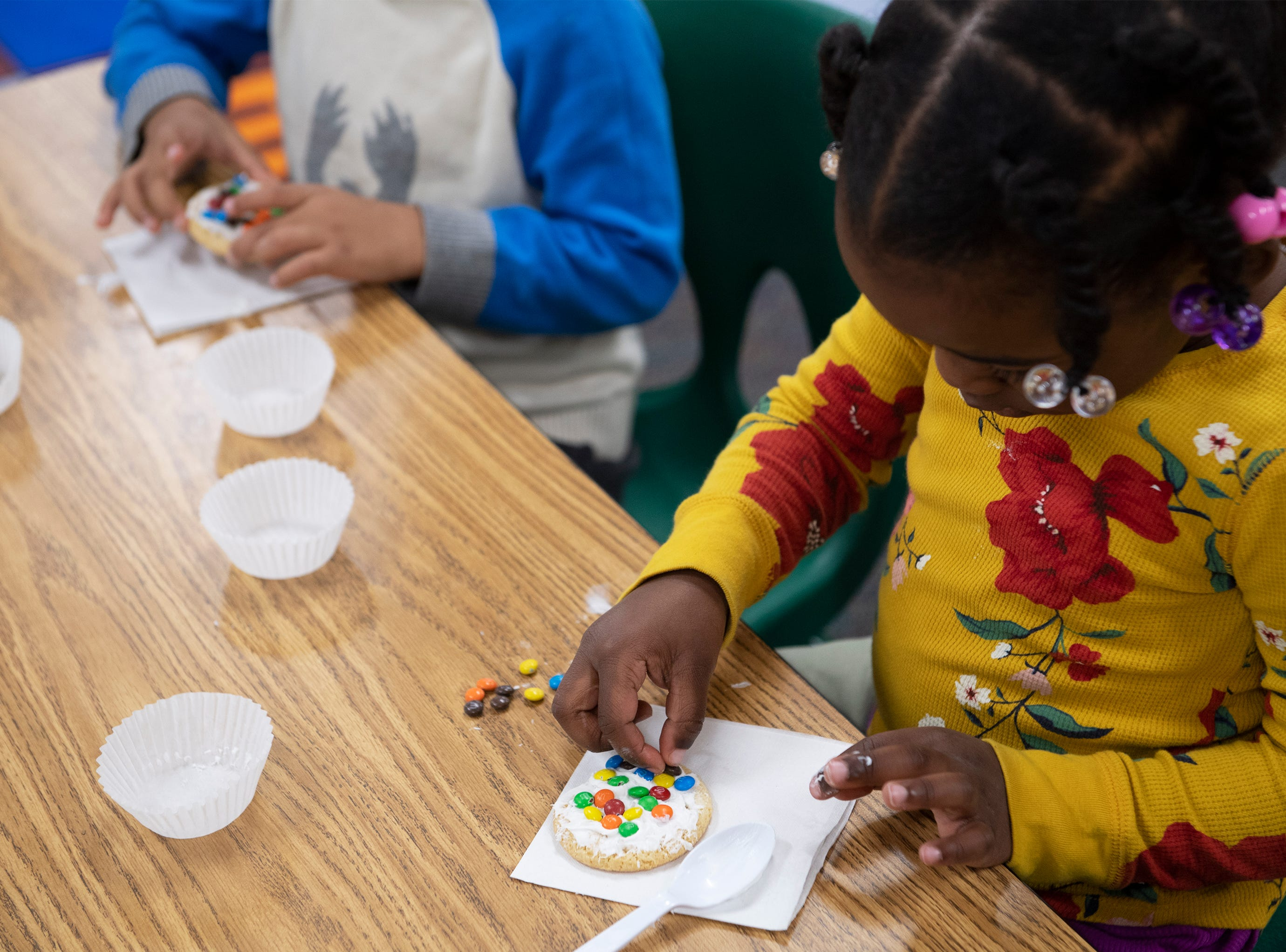 Janai Johnson, 4, decorates a cookie during an activity with Michelin volunteers at East North Street Academy Tuesday, Jan. 15, 2019.