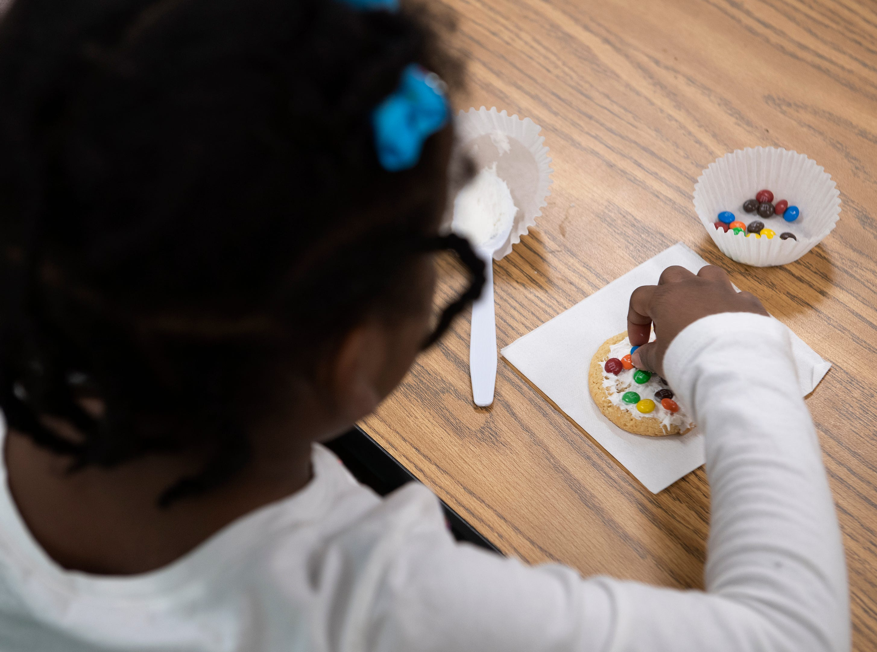 Chelsea Patterson, 4, decorates a cookie during an activity with Michelin volunteers at East North Street Academy Tuesday, Jan. 15, 2019.