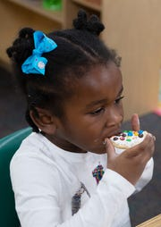 Chelsea Patterson, 4, eats a cookie after decorating it during an activity with Michelin volunteers at East North Street Academy Tuesday, Jan. 15, 2019.
