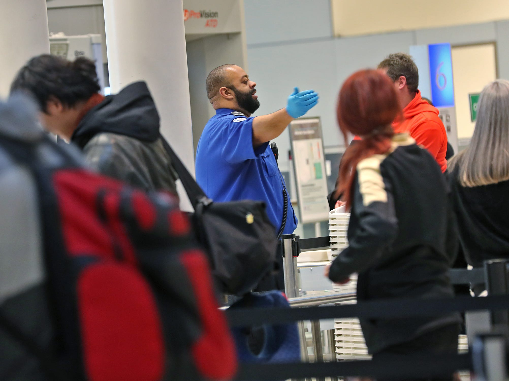 A TSA agent instruct travelers going through security at the Indianapolis International Airport, Tuesday, Jan. 15, 2019.