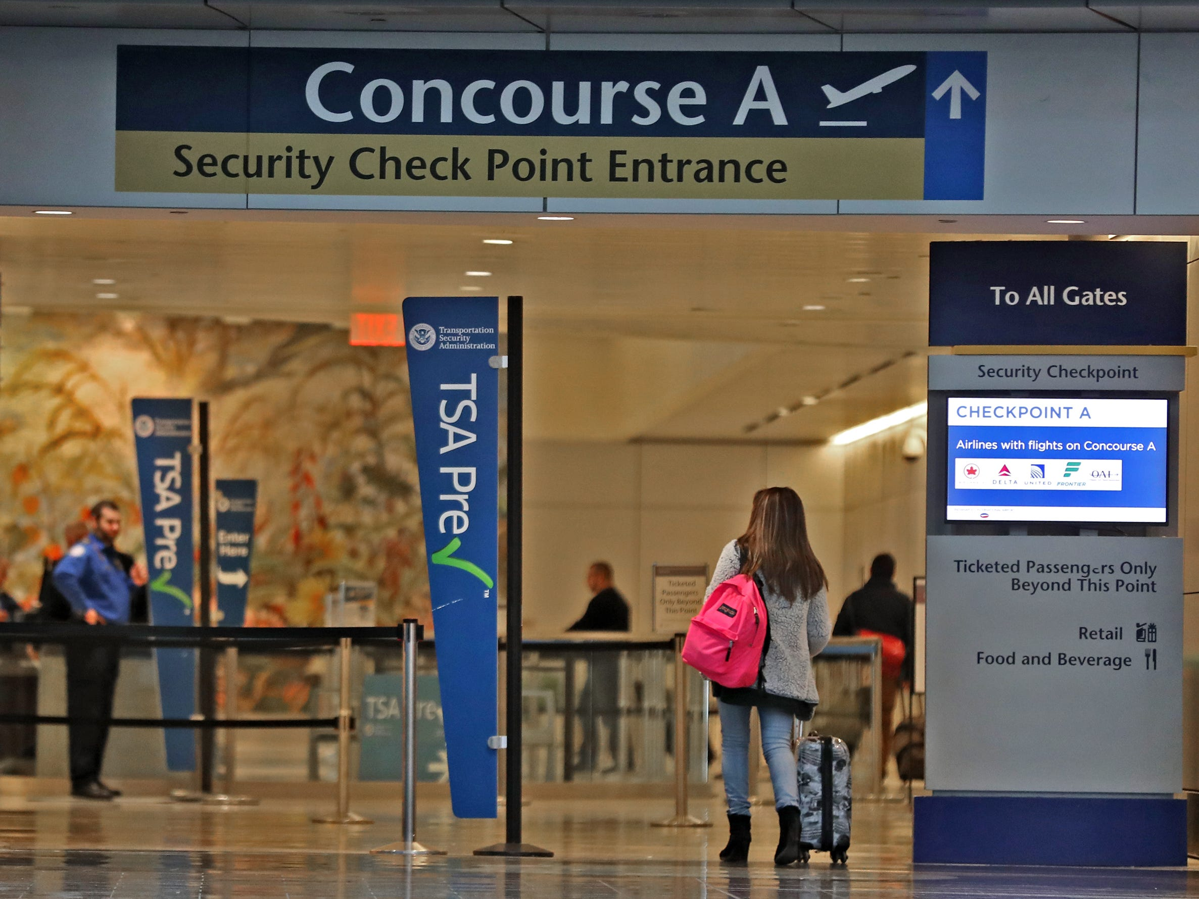 Travelers head to Security before travel at the Indianapolis International Airport, Tuesday, Jan. 15, 2019.