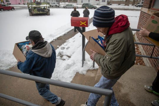 Clients and volunteers take food to waiting cars outside a food pantry run by Gleaners and Anthem, in Lebanon, Tuesday, Jan. 15, 2019. This is the first week for the pantry in this rural community.