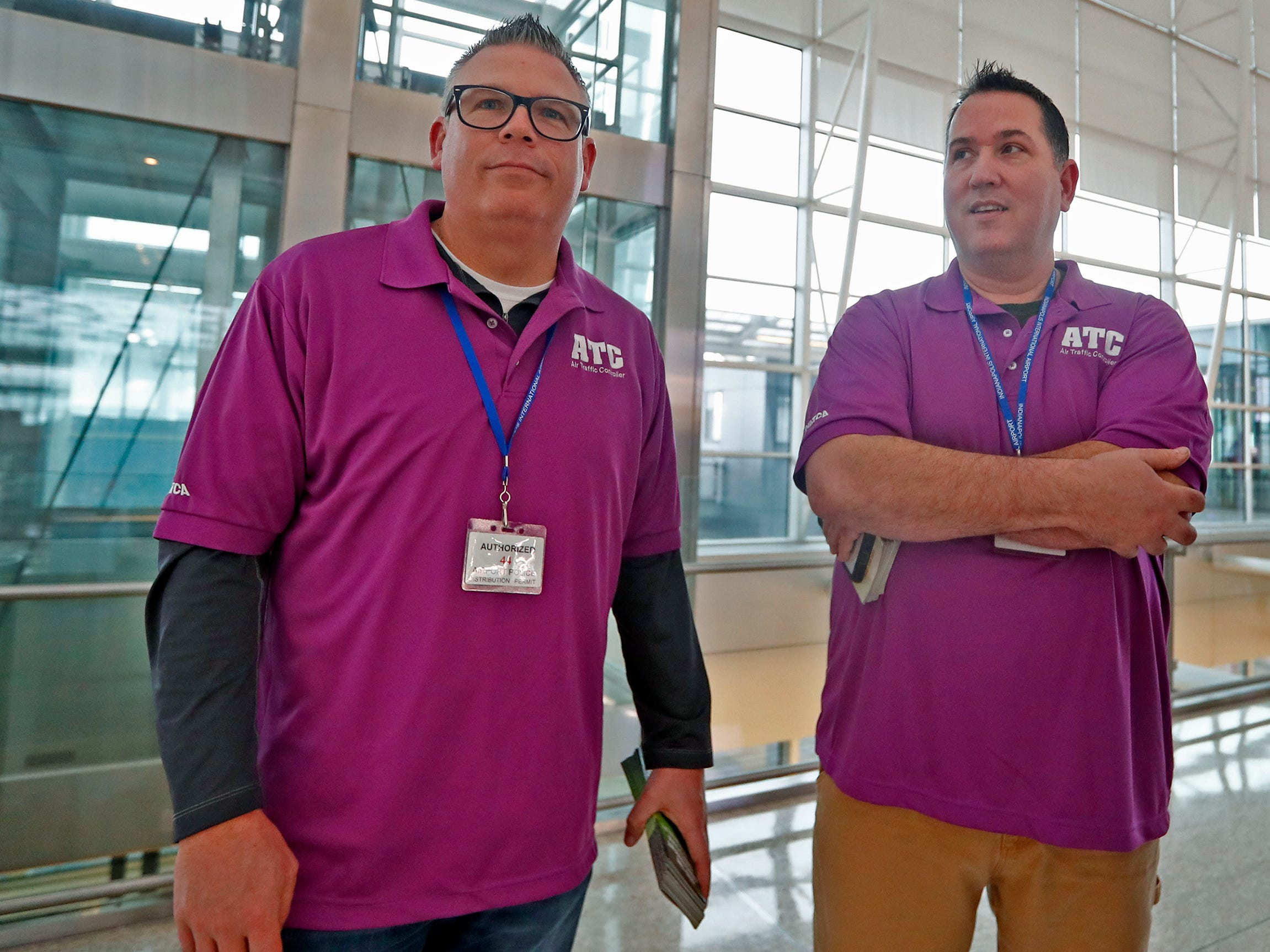 Drew MacQueen, left, Great Lakes Region Vice President for the NATCA, and Marc Schneider, Facilities Representative for Indianapolis, oversee air traffickers handing out information at the Indianapolis International Airport, Tuesday, Jan. 15, 2019.  Members of the National Air Traffic Controllers Association (NATCA) handed out the pamphlets to travelers to ask for the end of the government shutdown and to list ways the shutdown has affected the aviation safety.