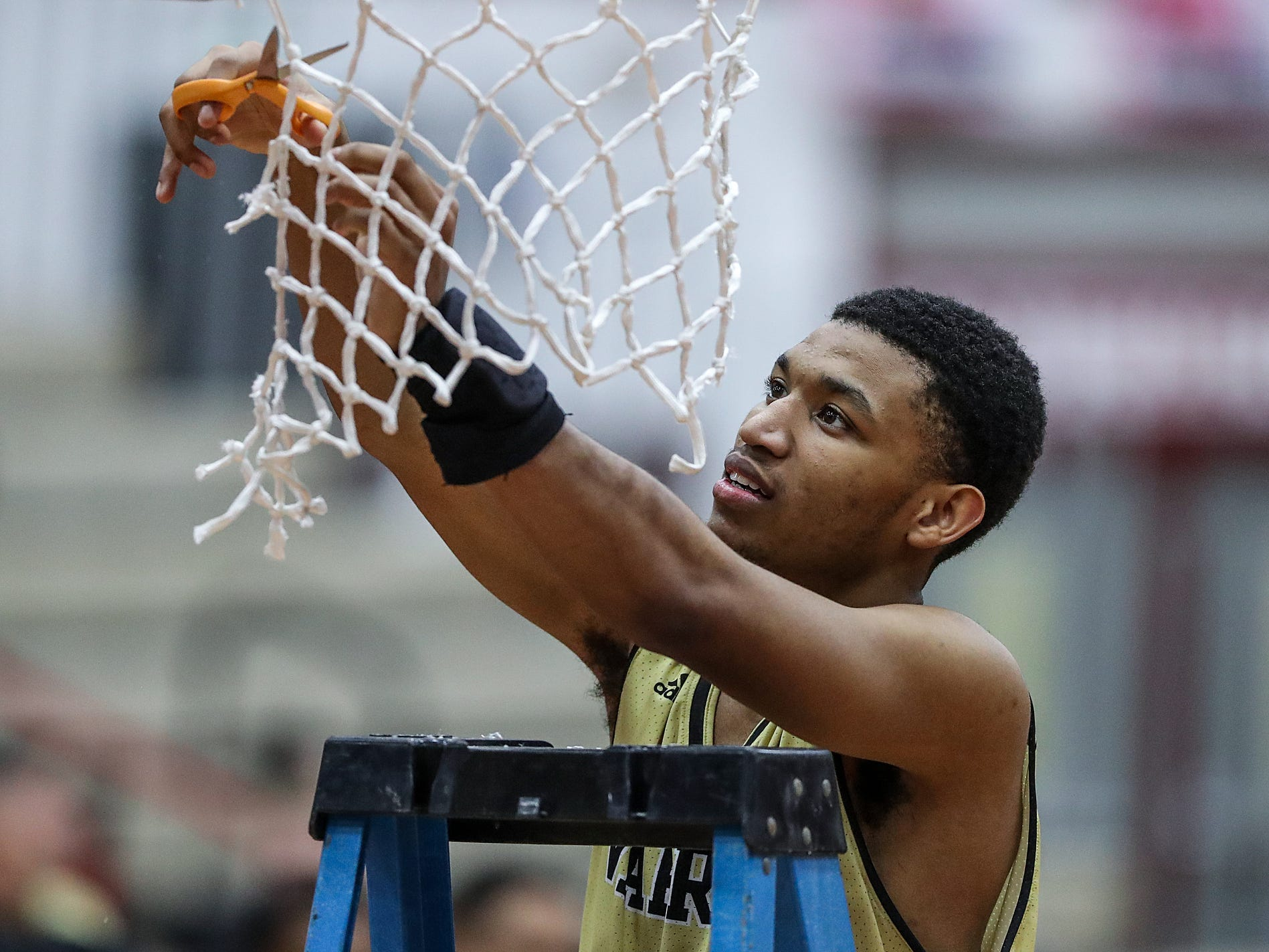 Warren Central Warriors guard Isiah Moore (20) cuts down a piece of the net after the Warriors won the Marion County tournament title at Southport High School in Indianapolis, Monday, Jan. 14, 2019. The victory marks a 46-game winning streak for the Warriors, the third-longest in state history.