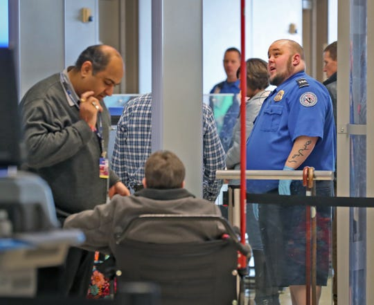 A TSA agent watches travelers going through security at the Indianapolis International Airport, Tuesday, Jan. 15, 2019.