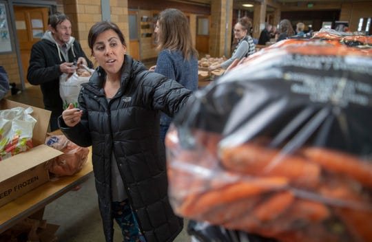 Gabi Youran, a volunteer from Zionsville, grabs a giant bag of carrots for a client who has a horse at a food pantry run by Gleaners and Anthem, in Lebanon, Tuesday, Jan. 15, 2019. This is the first week for the pantry in this rural community.