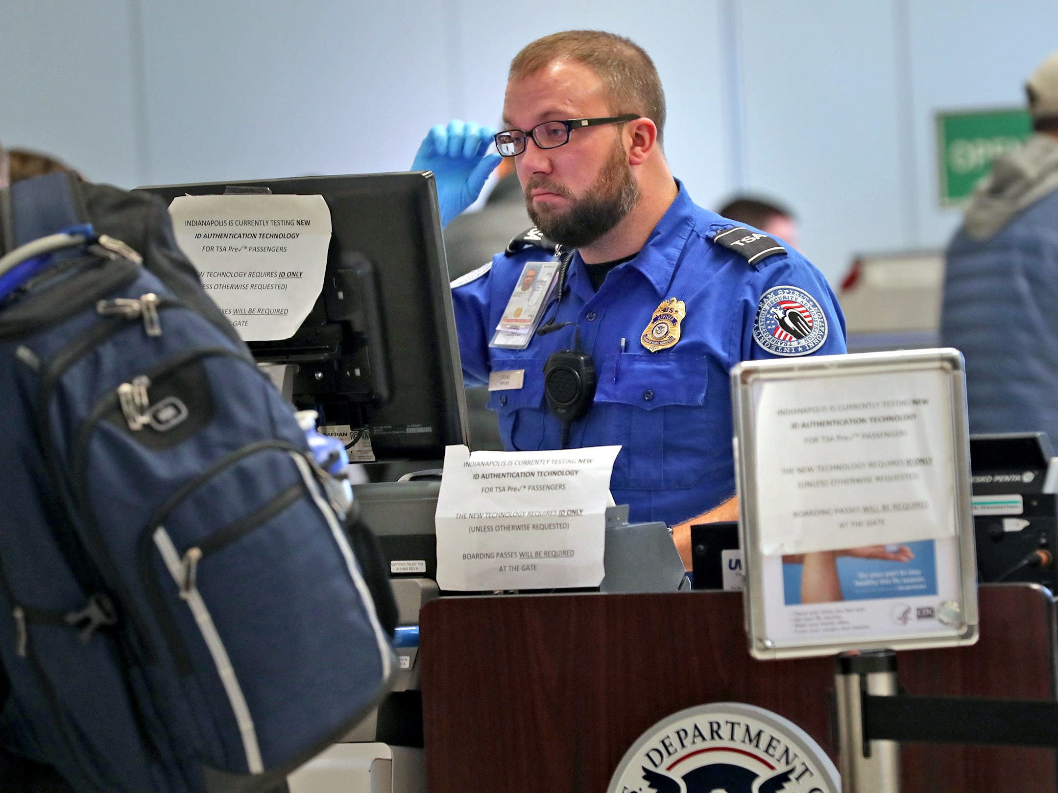 A TSA agent checks the ID of a traveler at the Indianapolis International Airport, Tuesday, Jan. 15, 2019.