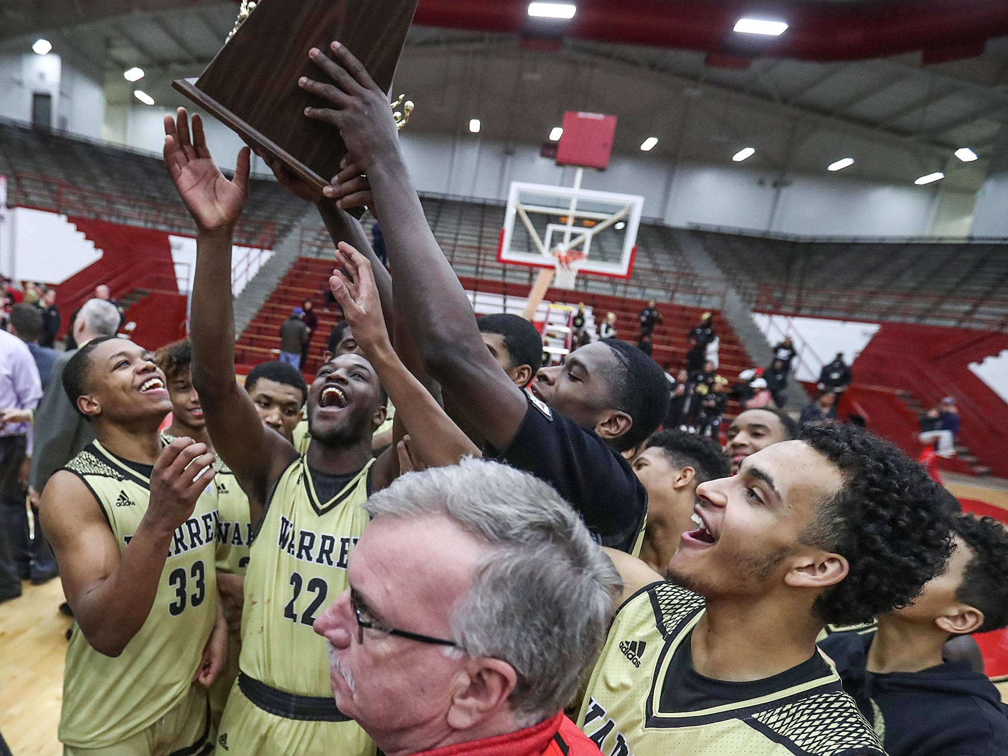 The Warren Central Warriors hold up the trophy after winning the Marion County tournament title at Southport High School in Indianapolis, Monday, Jan. 14, 2019. The victory marks a 46-game winning streak for the Warriors, the third-longest in state history.