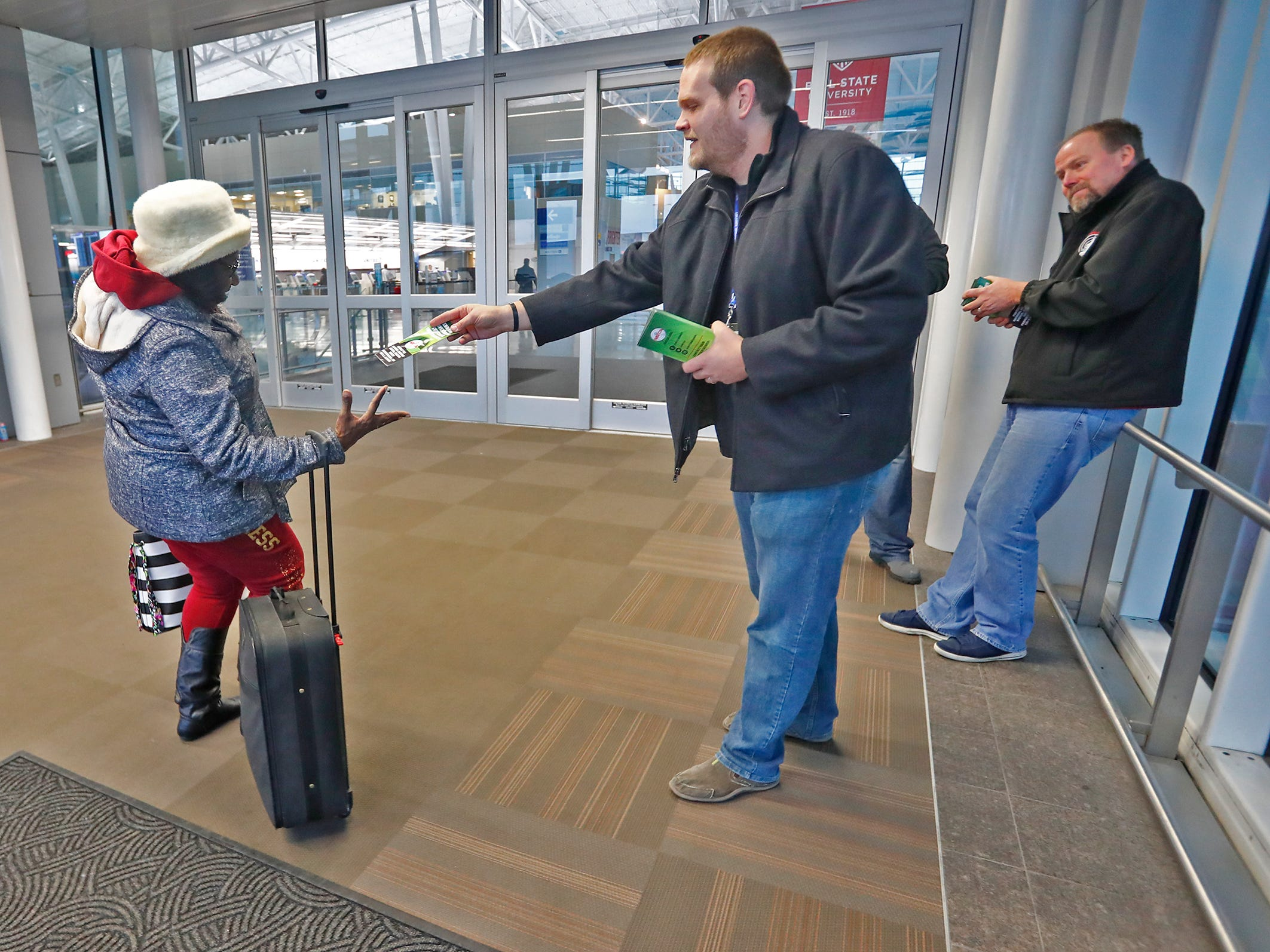 Air Traffic Control Specialist Aaron McCreery, center, hands out a pamphlet to a traveler at the Indianapolis International Airport, Tuesday, Jan. 15, 2019.  Air Traffic Control Specialist Beau Brown, right, also is on hand to distribute information.  Members of the National Air Traffic Controllers Association (NATCA) handed out the pamphlets to travelers to ask for the end of the government shutdown and to list ways the shutdown has affected the aviation safety.  Beau Brown