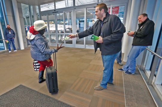Air Traffic Control Specialist Aaron McCreery, center, hands out a pamphlet to a traveler at the Indianapolis International Airport on Jan. 15 during the partial government shutdown. Air Traffic Control Specialist Beau Brown, right, also is on hand to distribute information.