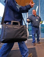 Air traffic control specialist Mark Dipalmo hands a pamphlet to a traveler at the Indianapolis International Airport on Tuesday.