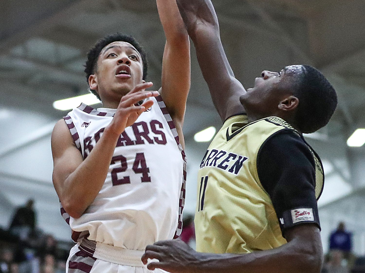Warren Central Warriors forward Jesse Bingham (11) tries to stop a shot by Lawrence Central Bears Nijel Pack (24) in the first half of Marion County tournament finals at Southport High School in Indianapolis, Monday, Jan. 14, 2019. Warren Central won the title, 60-56.