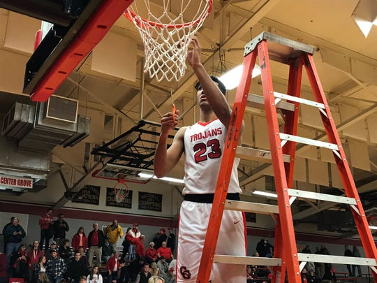 Trojans big man Trayce Jackson-Davis cuts down his piece of the net after Center Grove won the Johnson County tournament title Monday night at Edinburgh.