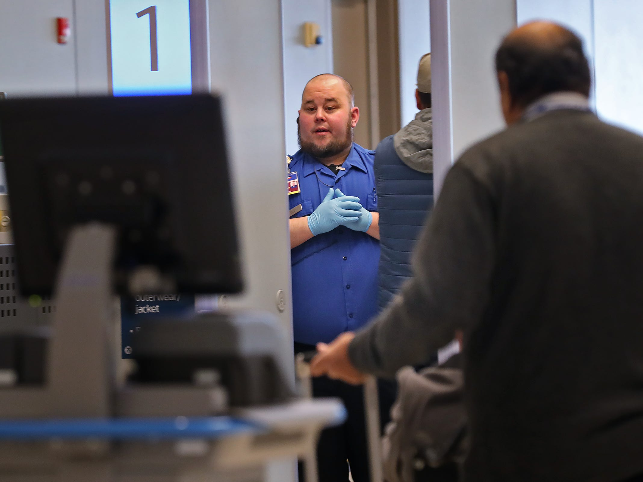 A TSA agent instructs a traveler going through security at the Indianapolis International Airport, Tuesday, Jan. 15, 2019.