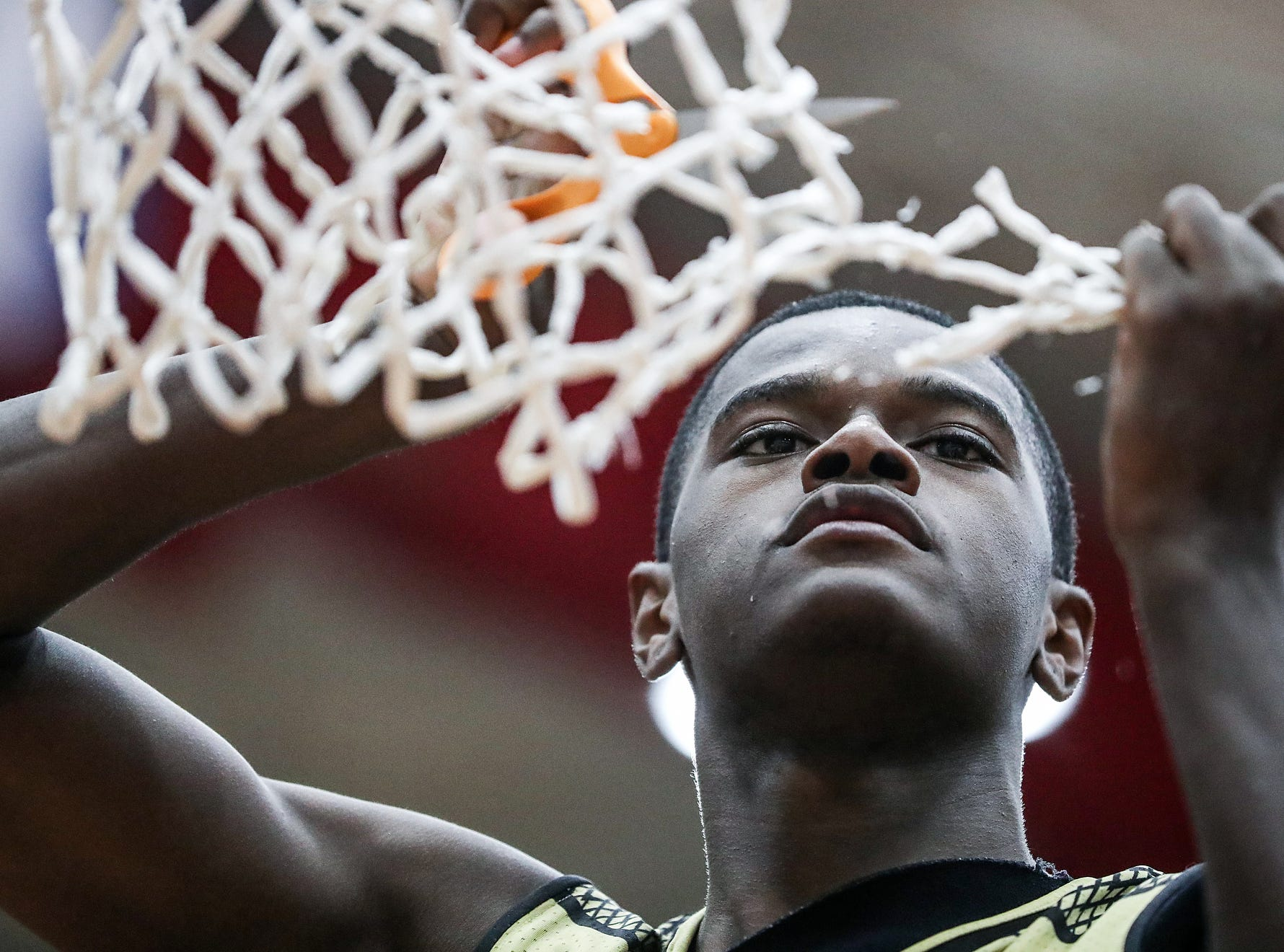 Warren Central Warriors forward Jesse Bingham (11) cuts down a piece of the net after the Warriors took the Marion County tournament title at Southport High School in Indianapolis, Monday, Jan. 14, 2019. The victory marks a 46-game winning streak for the Warriors, the third-longest in state history.