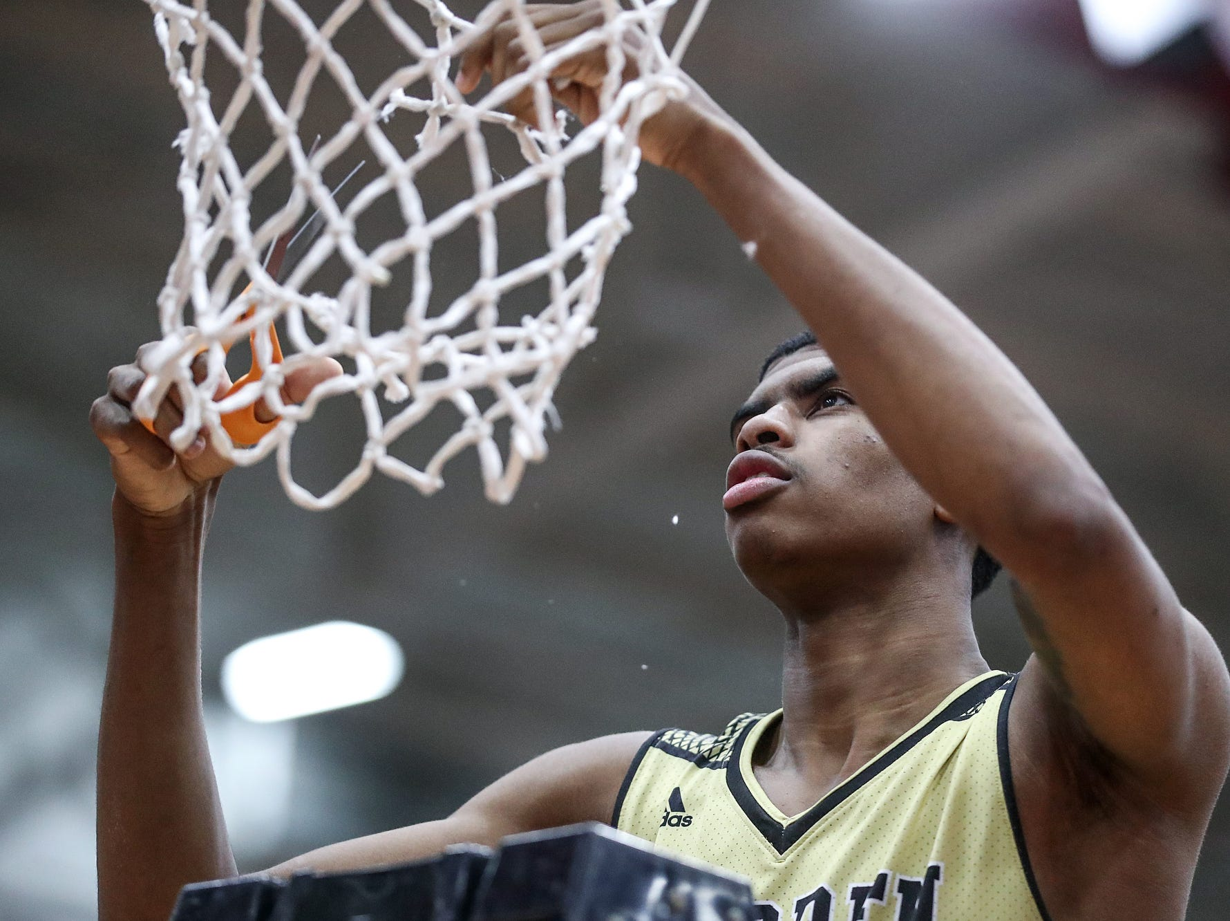 Warren Central Warriors forward Jakobie Robinson (23) cuts down a piece of the net after the Warriors won the Marion County tournament title at Southport High School in Indianapolis, Monday, Jan. 14, 2019. The victory marks a 46-game winning streak for the Warriors, the third-longest in state history.