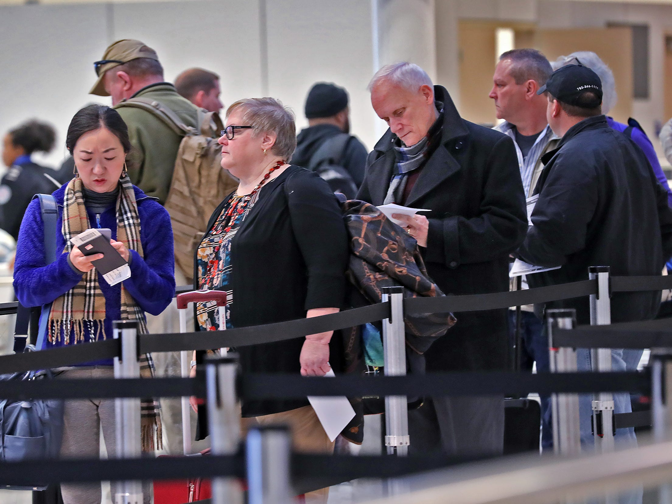 Travelers wait to go through security at the Indianapolis International Airport, Tuesday, Jan. 15, 2019.