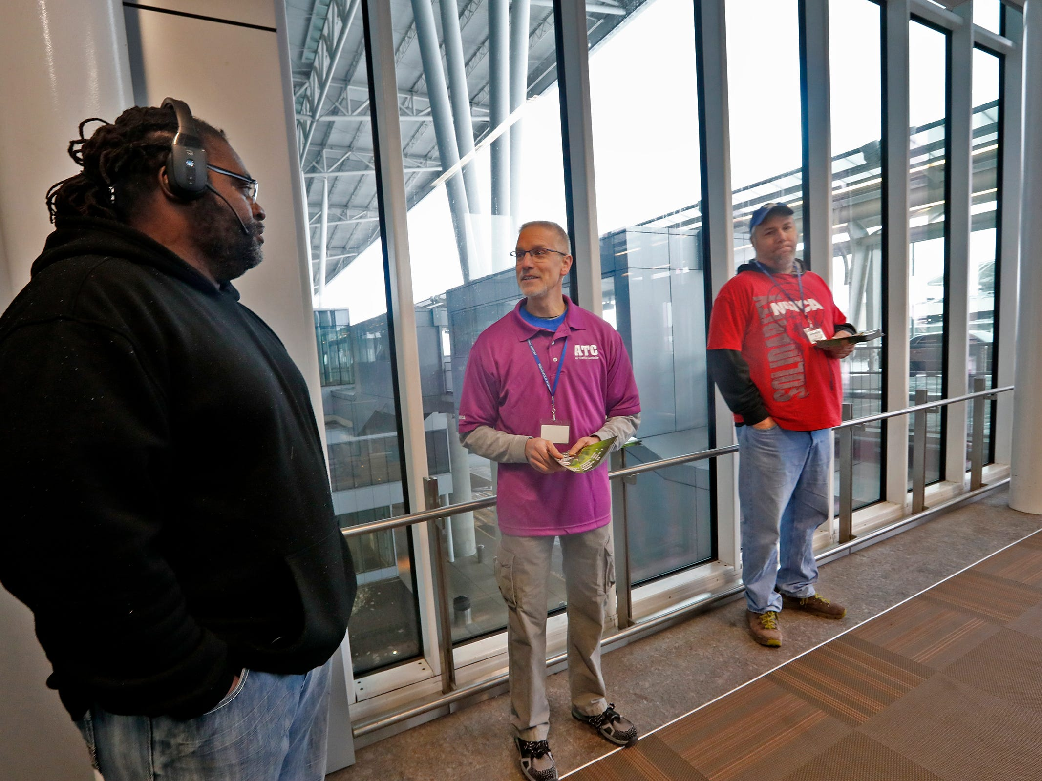 "Roger Bell, left, talks with Air Traffic Control Specialist Mark Wittmayer, center, at the Indianapolis International Airport, Tuesday, Jan. 15, 2019.  Members of the National Air Traffic Controllers Association (NATCA) handed out the pamphlets to travelers to ask for the end of the government shutdown and to list ways the shutdown has affected the aviation safety.  Everyone wants safe borders says Wittmayer, but ""right now it's about paying the bills so that we can put food on the table for our families."""