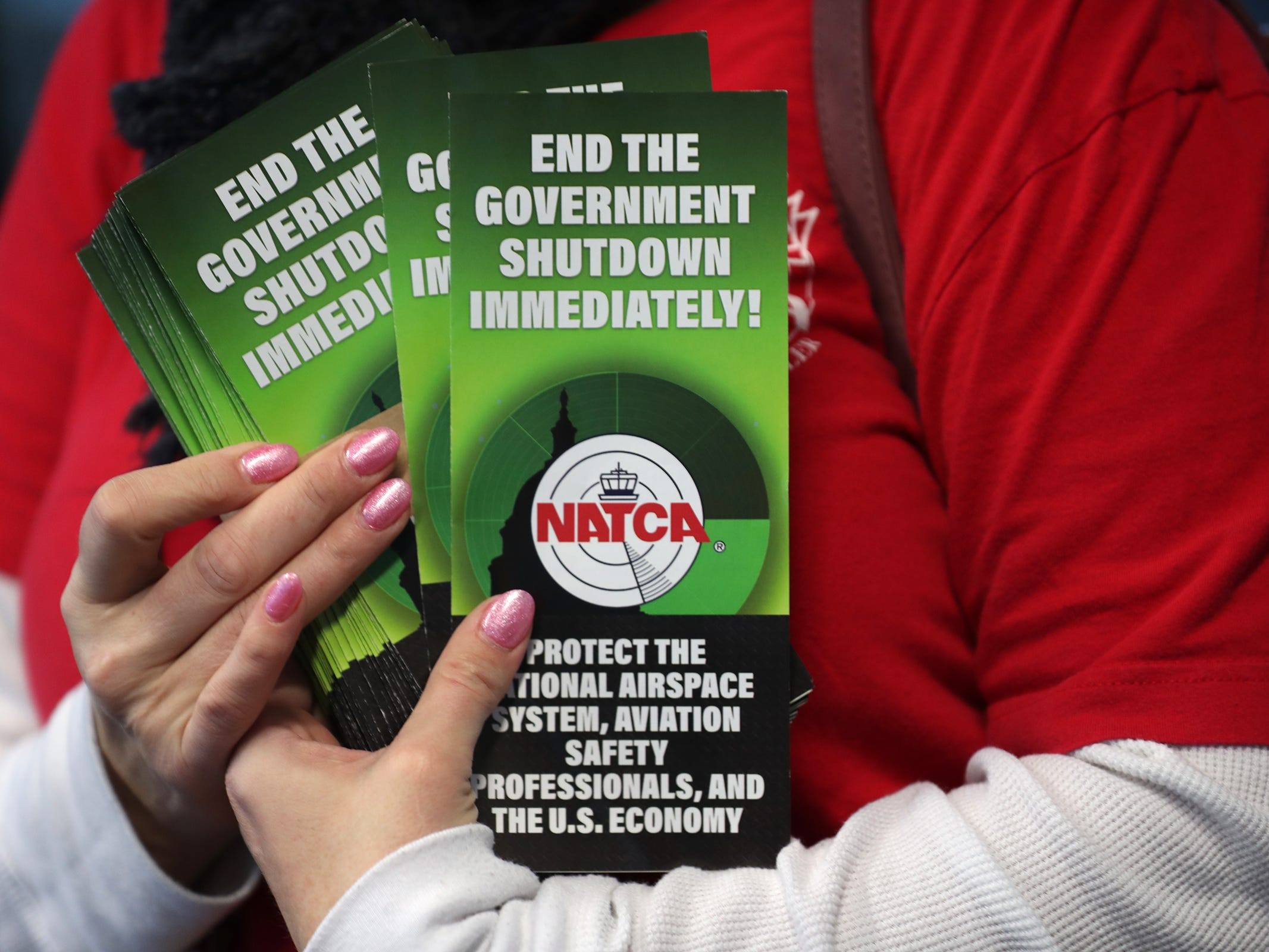 Pamphlets from the NATCA are given to travelers at the Indianapolis International Airport, Tuesday, Jan. 15, 2019.  Members of the National Air Traffic Controllers Association (NATCA) handed out the pamphlets to travelers to ask for the end of the government shutdown and to list ways the shutdown has affected the aviation safety.