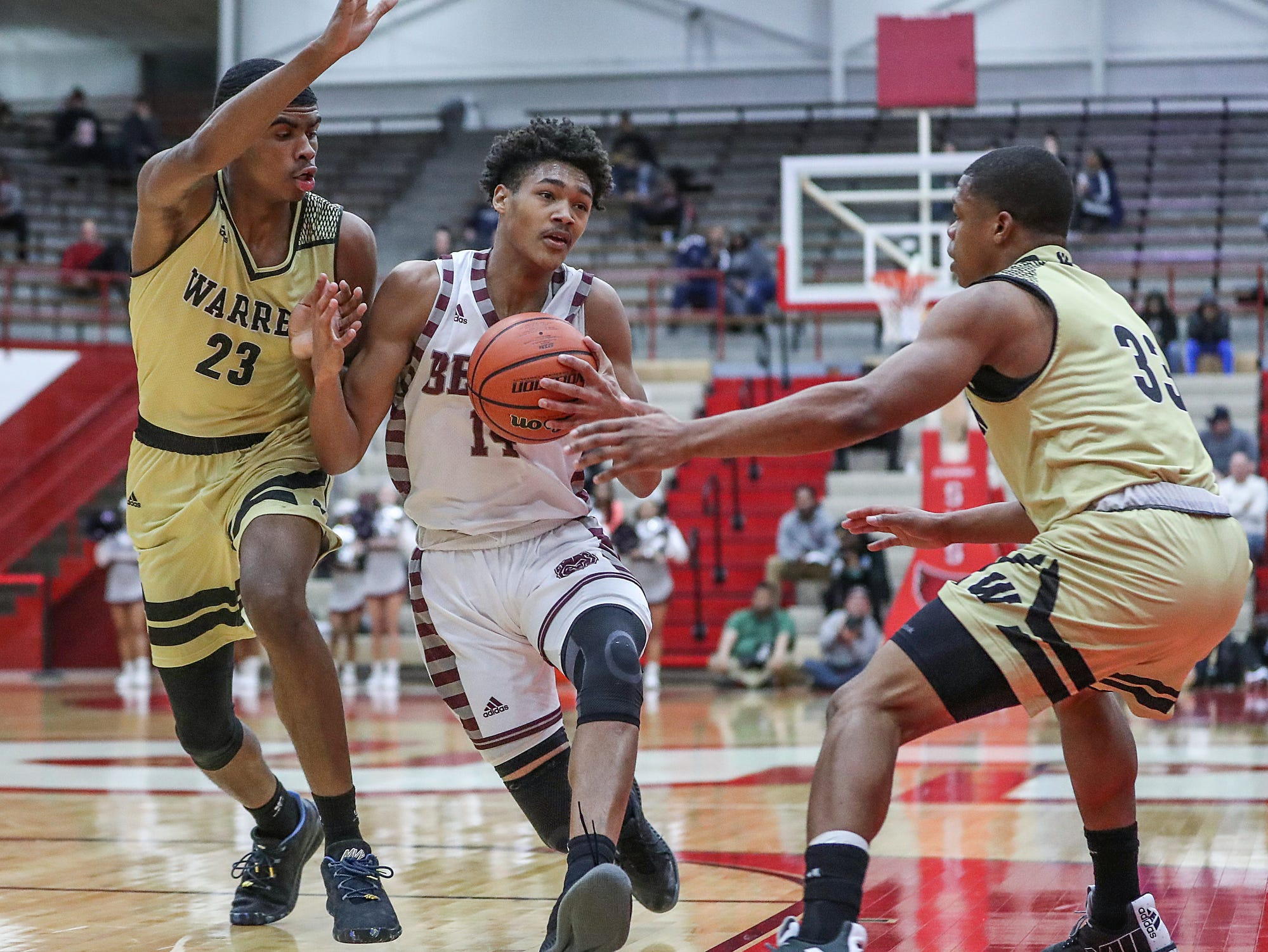 Lawrence Central Bears Dre Davis (14) breaks between warren Central defenders Jakobie Robinson (23) and Manuel Brown (33) in the first half of Marion County tournament finals at Southport High School in Indianapolis, Monday, Jan. 14, 2019.