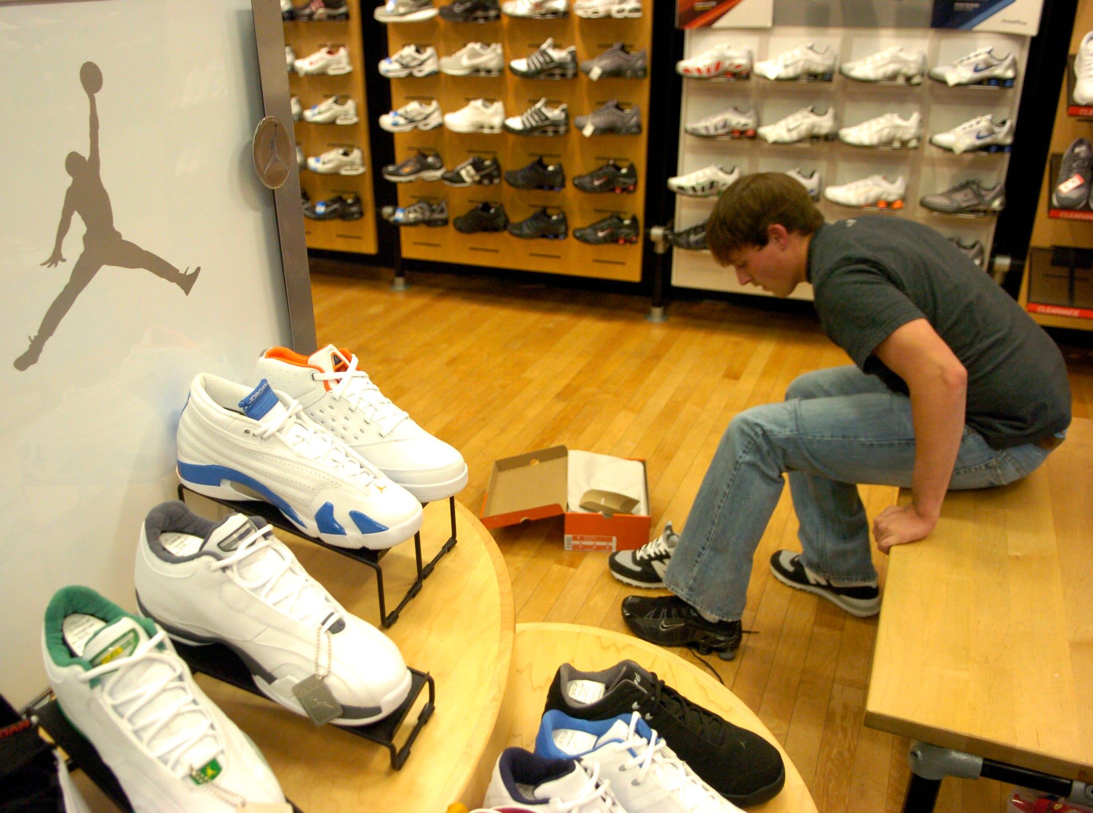 Twenty year-old Kevin McKamey tries on a pair of Nike Shox at the Finish Line store in West Town Mall.