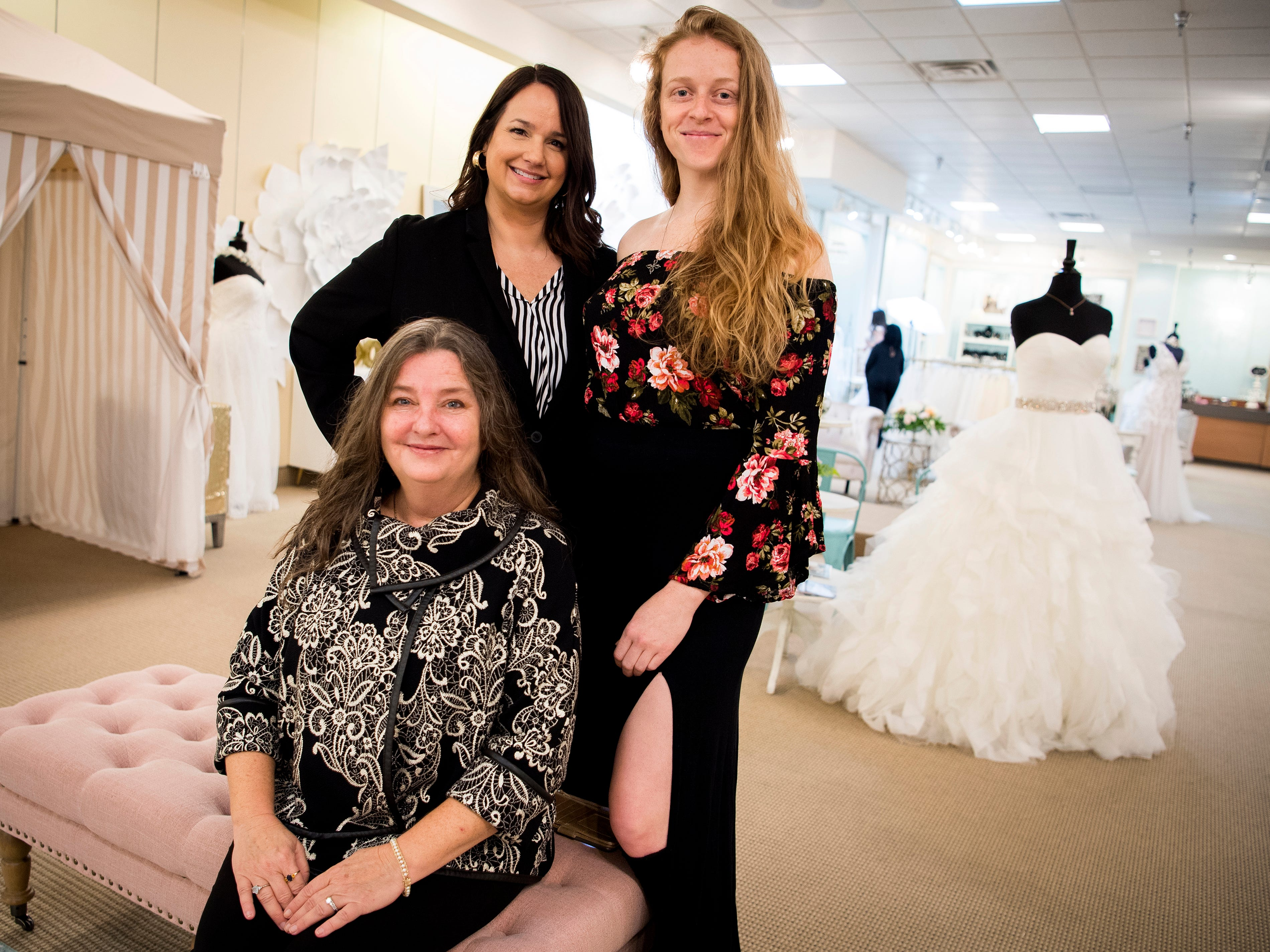 Owner Jacqui Wadsworth, bottom left, with sister Elizabeth Ethridge, top left, and daughter Grace Alexander, right, at The Gilded Gown at Knoxville Center Mall on Monday, January 14, 2019.