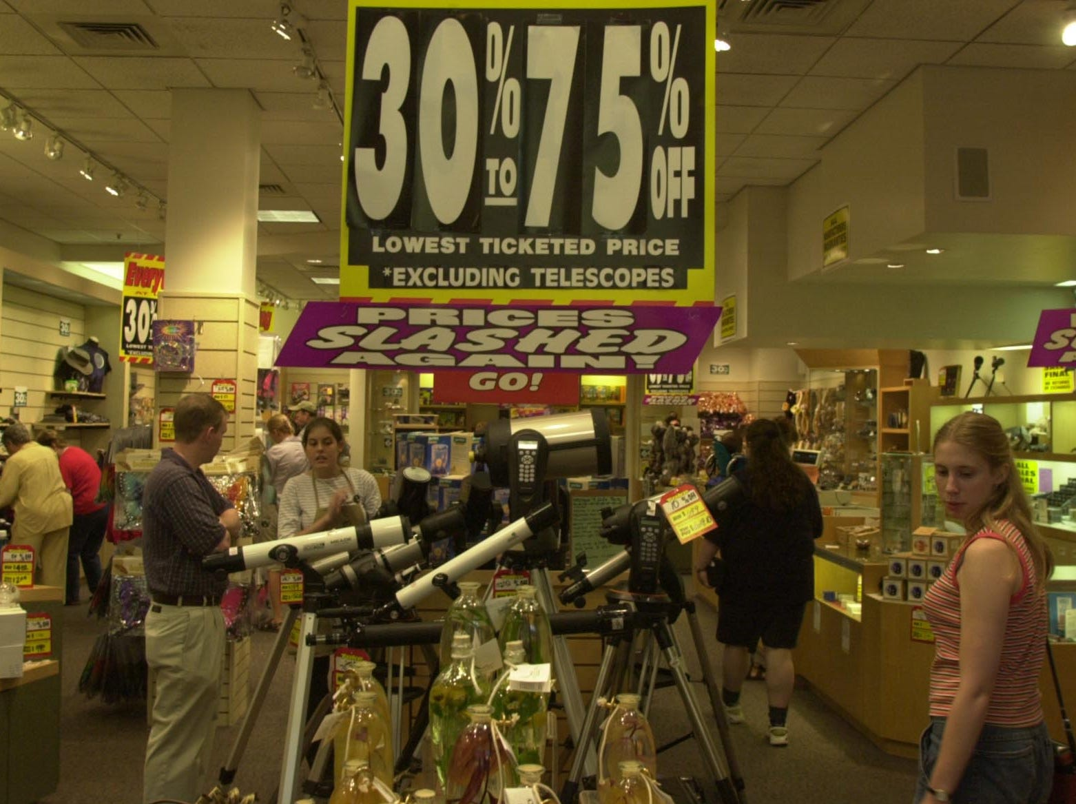 Carissa Magnusson, right, looks at sale items at Natural Wonders in West Town Mall as a store employee Jennifer Huskey talks to Mike Thomas, center, about telescopes Wednesday.  Natural Wonders is the latest speciality store to go under at West Town , along with NASCAR, Warner Bros., and the WKOP-Public Television Store.