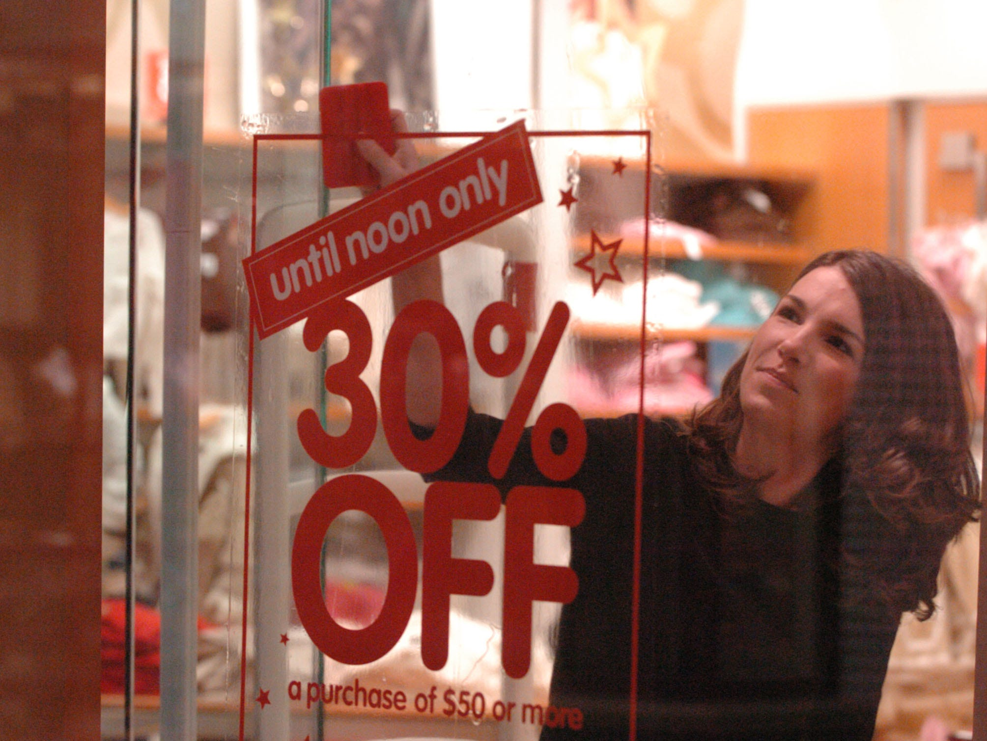 Kim Bloomfield puts a sale sign in the window of the West Town Mall Gap store early Friday morning.    The day after the Thanksgiving Day holiday started with shoppers lined up outside of Knoxville area retailers.  Many of the shoppers spent the night waiting in line for early bird prices or limited numbers of items.