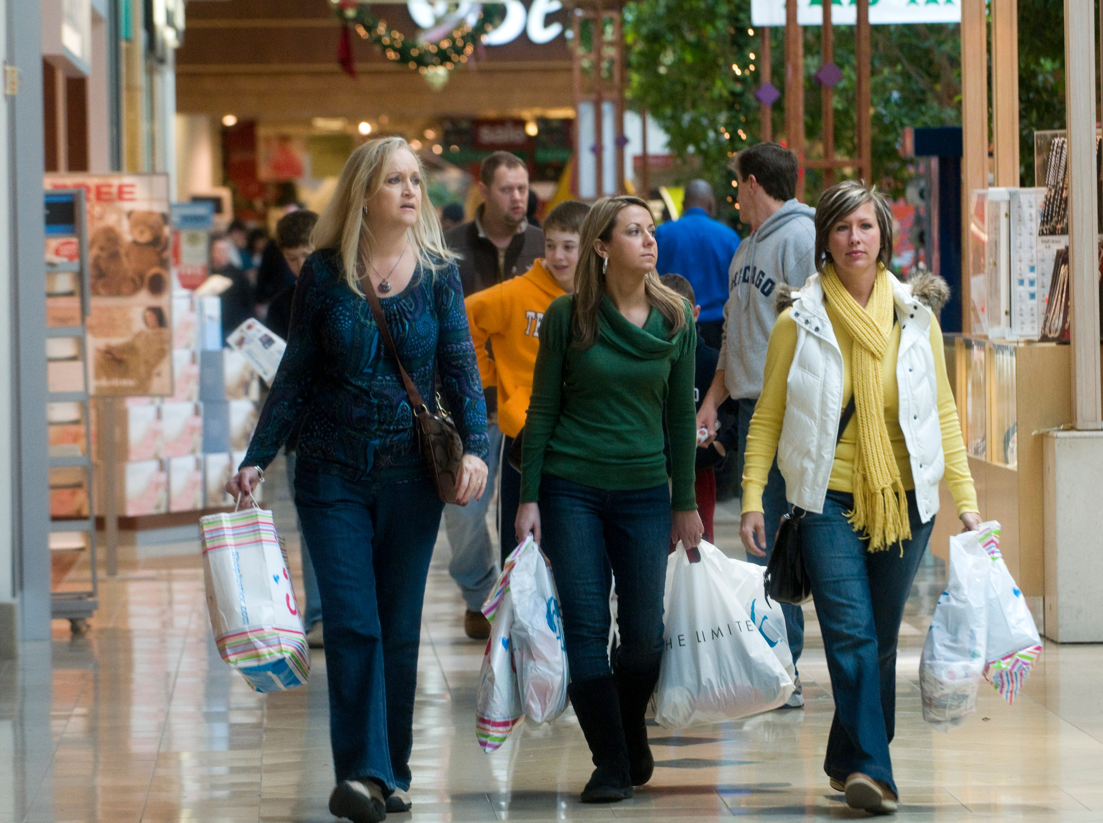 Kim Jackson, left, and her daughter in law Haley Jackson, center, and friend Kristie Dunlap carry packages Friday, Nov. 27, 2009 at West Town Mall. The three women started their Black Friday shopping spree at 5 a.m.