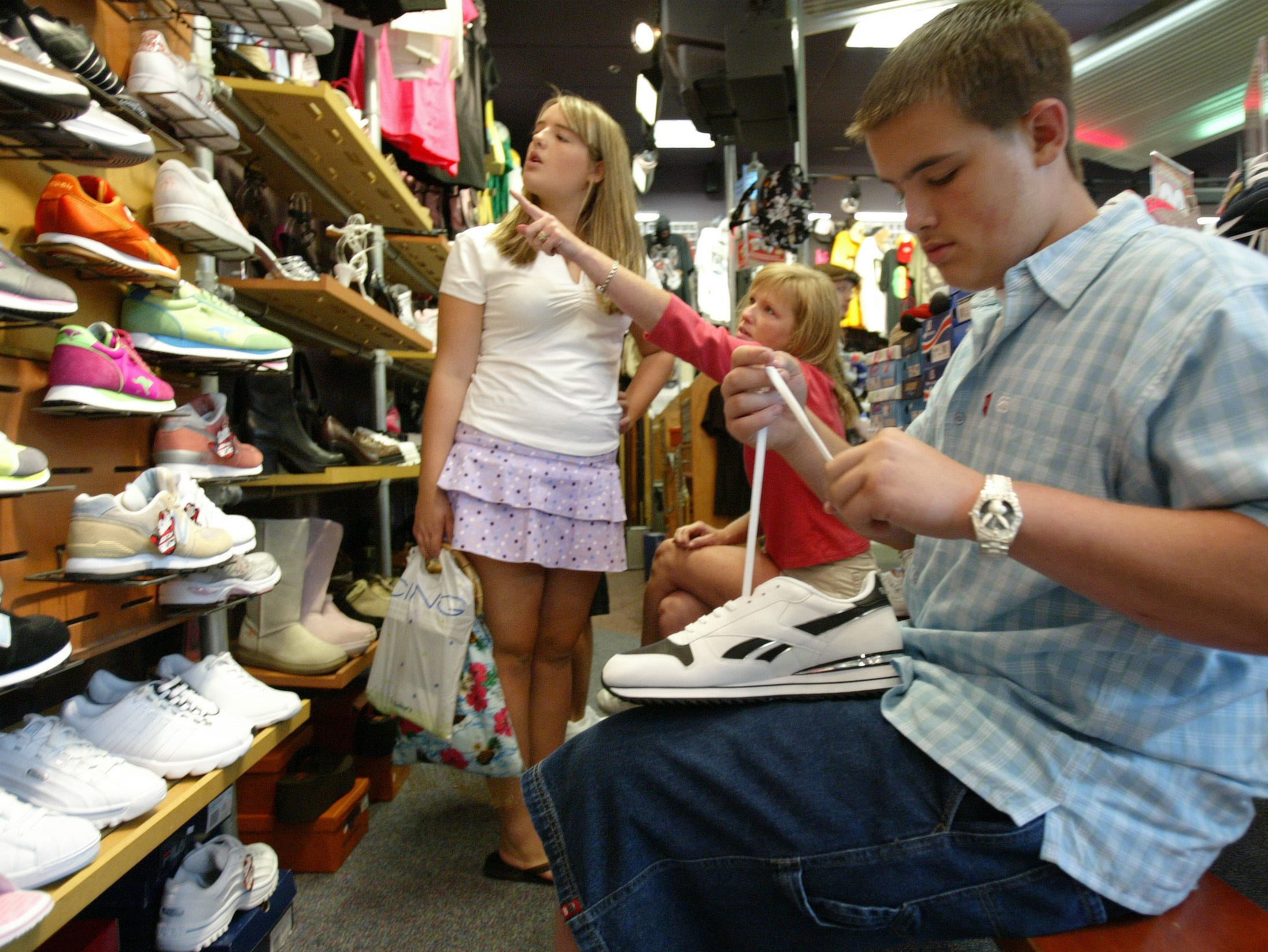 schoolbiz.CC#1752.JPG-----biz----Shopping for school shoes, Logan Kelley, 14, laces up his new tennis shoes while his mother Susan helps his sister Jeriel, 13, find a pair of shoes. The Kelleys are from Loudon and were shopping on Saturday at Journeys shoe store in West Town Mall.