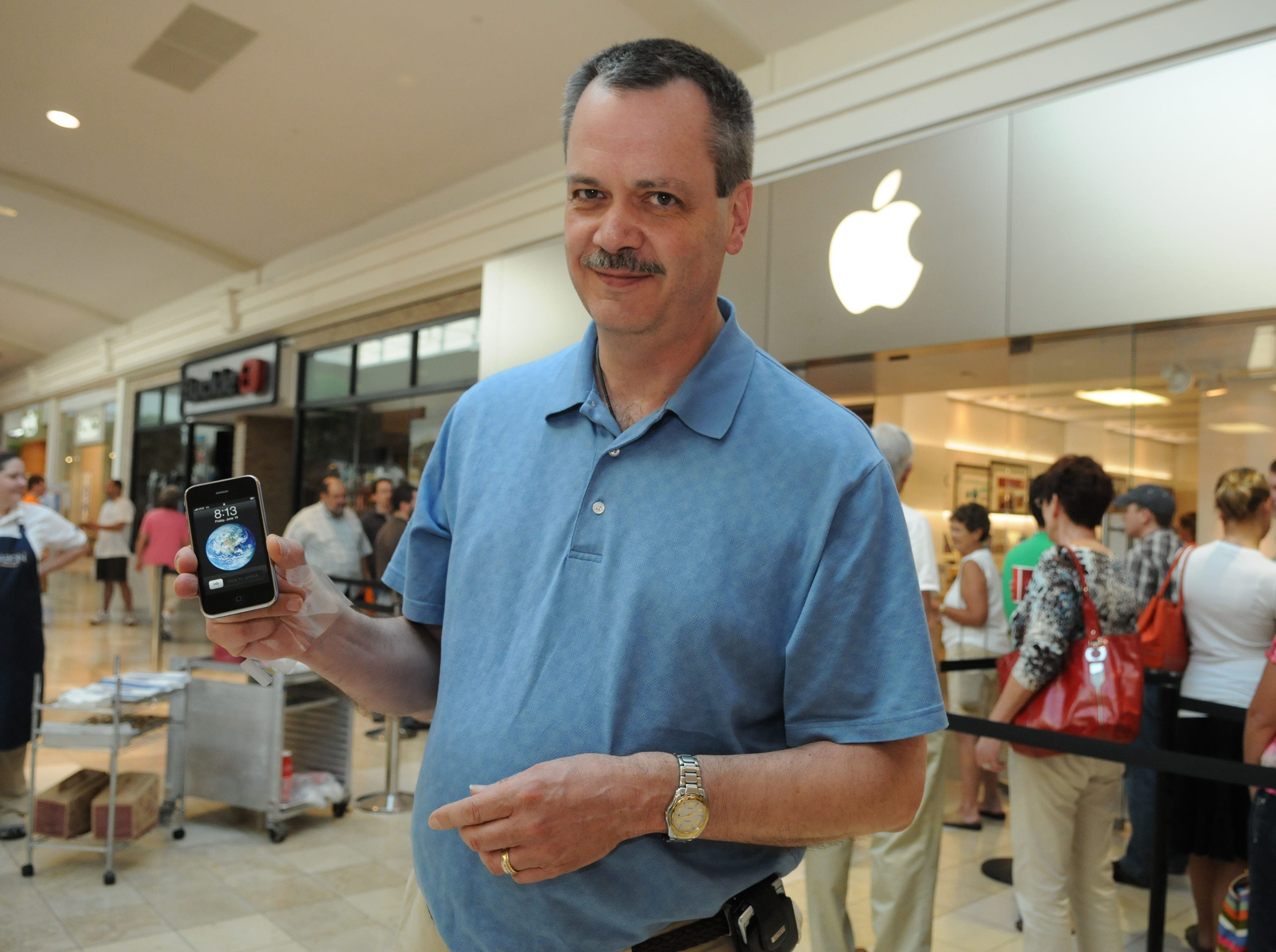 Bob Kreisa of Halls holds his new iPhone outside the Apple Store in West Town Mall Friday morning. The new Apple iPhone launches at the local Apple store in West Town Mall and at ATT stores.   - Friday, June 19, 2009