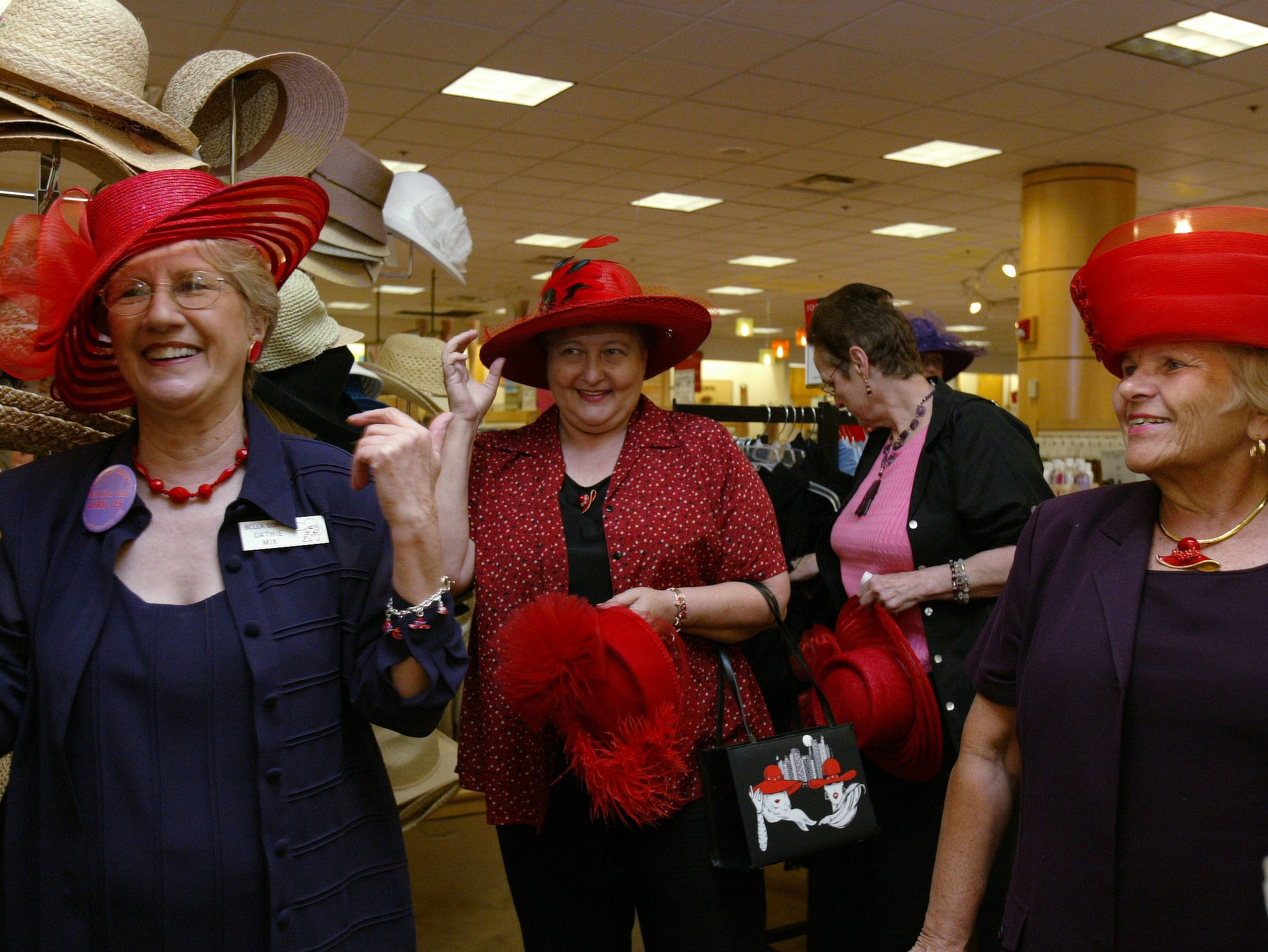 Cathie Mix, left, laughs as she tries on a red hat along with Elizabeth Jett, Jackie Pavelka and Camille Cook at Proffitt's in West Town Mall on Sunday. Mix, Jett and Cook are members of the Red Hat Society, a national organization dedicated to making midlife fun.