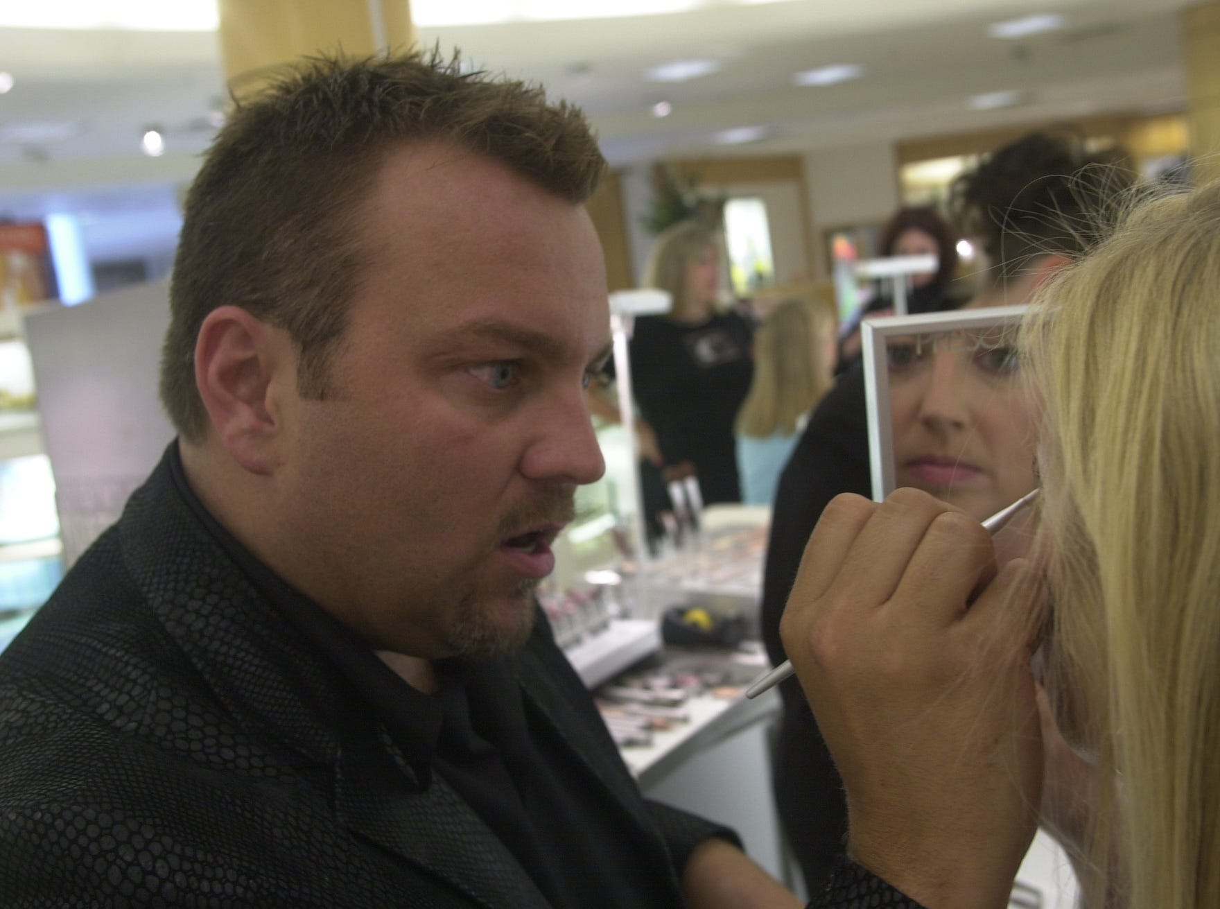 Prescriptives make-up artist John Hurley practices his trade on customer Catherine Skanks Wednesday at Proffitt's in West Town Mall.  Hurley has worked in the entertainment industry and for the National Junior Miss Pageant.