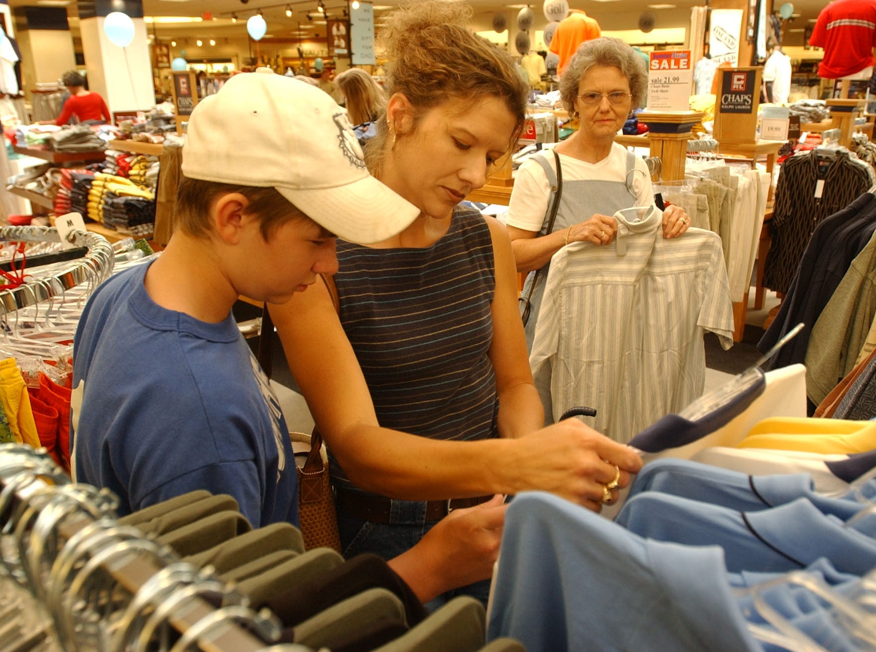 Jillisa Richards, center, helps her thirteen-year-old son Zac shop for a Father's Day present at Proffitt's in the West Town Mall Friday morning.  In the back is Richards' mother, Carolyn Colegrove also on their shopping trip.  (cq on Jillisa, Zac and Colegrove)   ASA200  2003 Image #DSC_8646.JPG