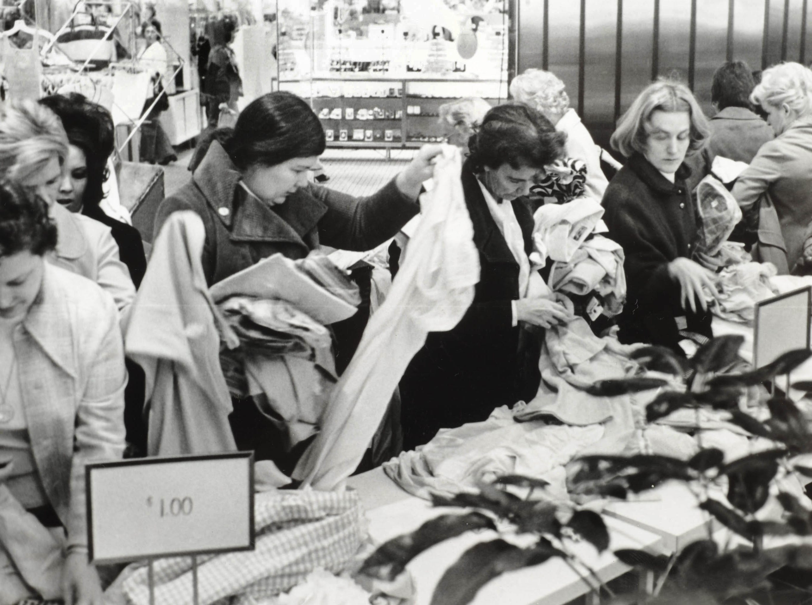 "In an Jan. 16, 1975, photograph, shoppers crowd a sales table at West Town Mall. ""It was every gal for herself at the $1 table at West Town's Sidewalk Sale as January bargain hunters converged on the Mall at door-opening time,"" according to the News-Sentinel's caption for the photo. (KNS Archive)"