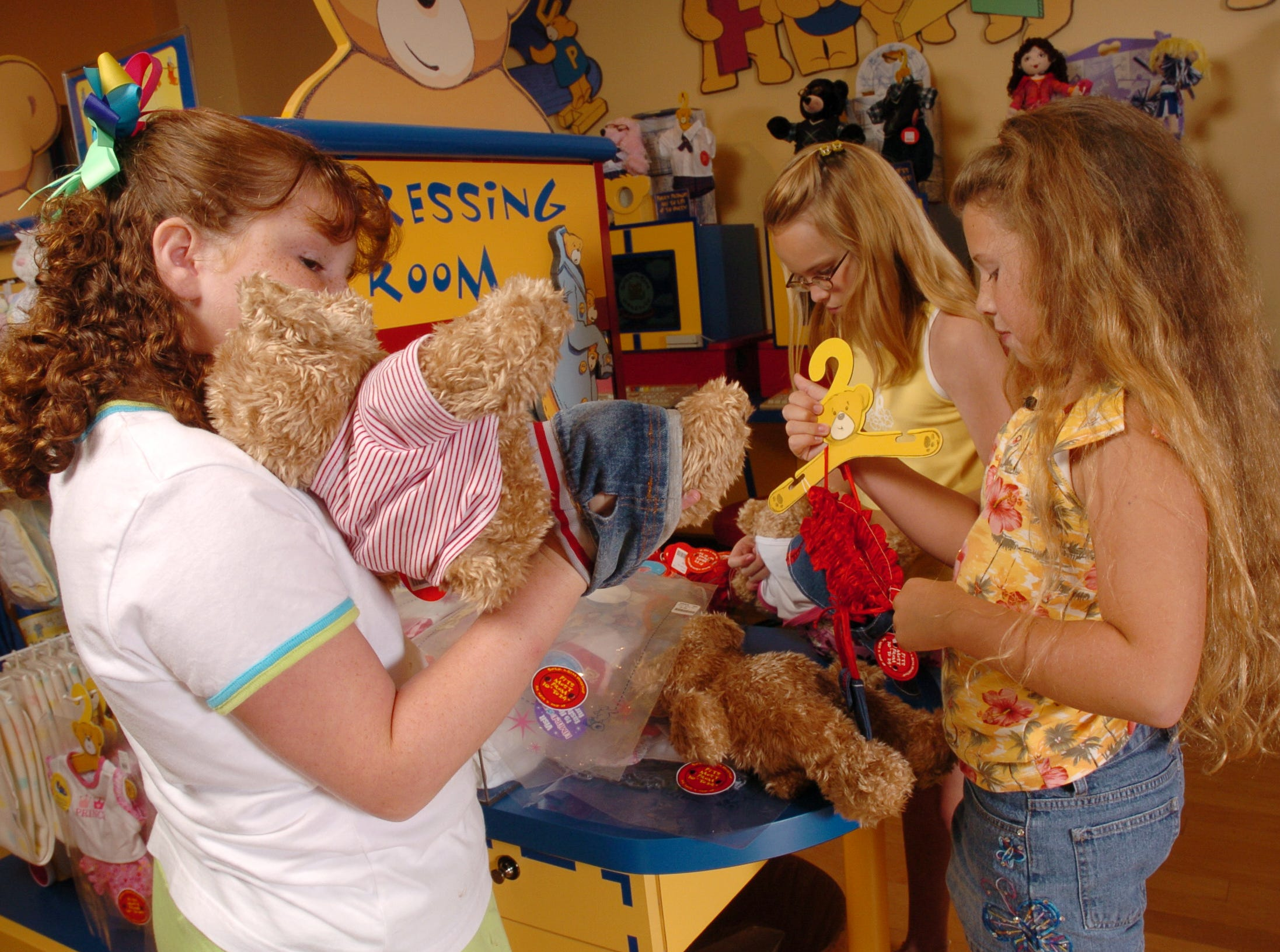 From left, Paige Van de Vuurst, 10, Katy Honeycutt, 9, and Caitlin Aiken, 9, outfit bears Thursday at the Build a Bear Workshop store in West Town Mall.  The girls are from Limestone, TN, and they collected enough money to buy 80 bears that they will give to children at Johnson City Medical Center. 8/5/2004