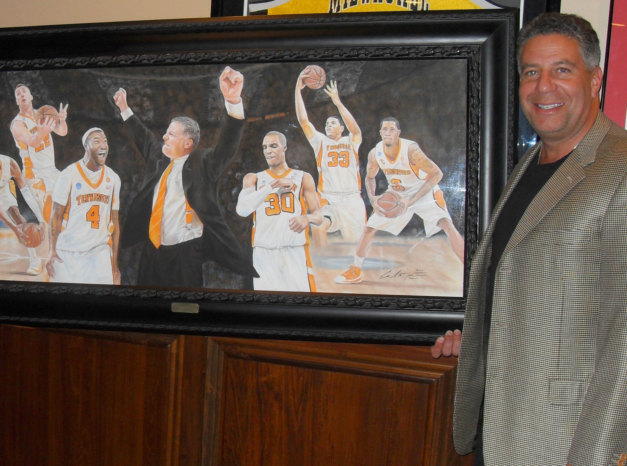 Artist Carl Hess presents UT men's coach Bruce Pearl with a portrait to commemorate the Elite Eight team at the basketball annual banquet on May 7. Prints of this portrait will be available at Hess' all-day fundraiser Saturday at West Town Mall.