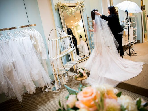 615d8e53cb3 A bride tries on a veil with a dress in the bridal trying on area at