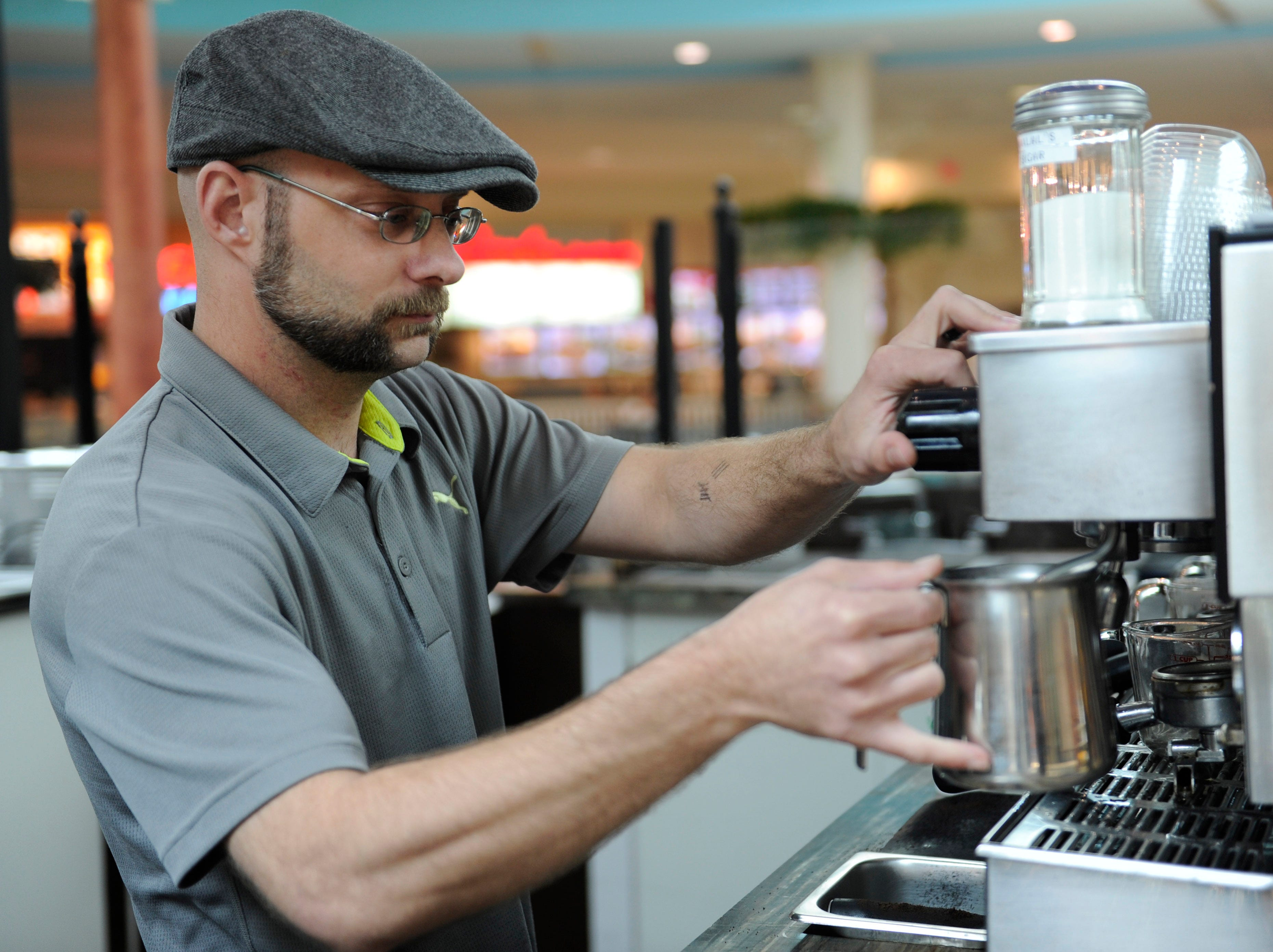 Jeremy Kendall with Javerde Coffee Company prepares a beverage in the West Town Mall food court on Tuesday, April 23, 2013. The locally owned Javerde is planning to close on Saturday, April 27. Starbucks Coffee is scheduled to open May 3rd near the food court.